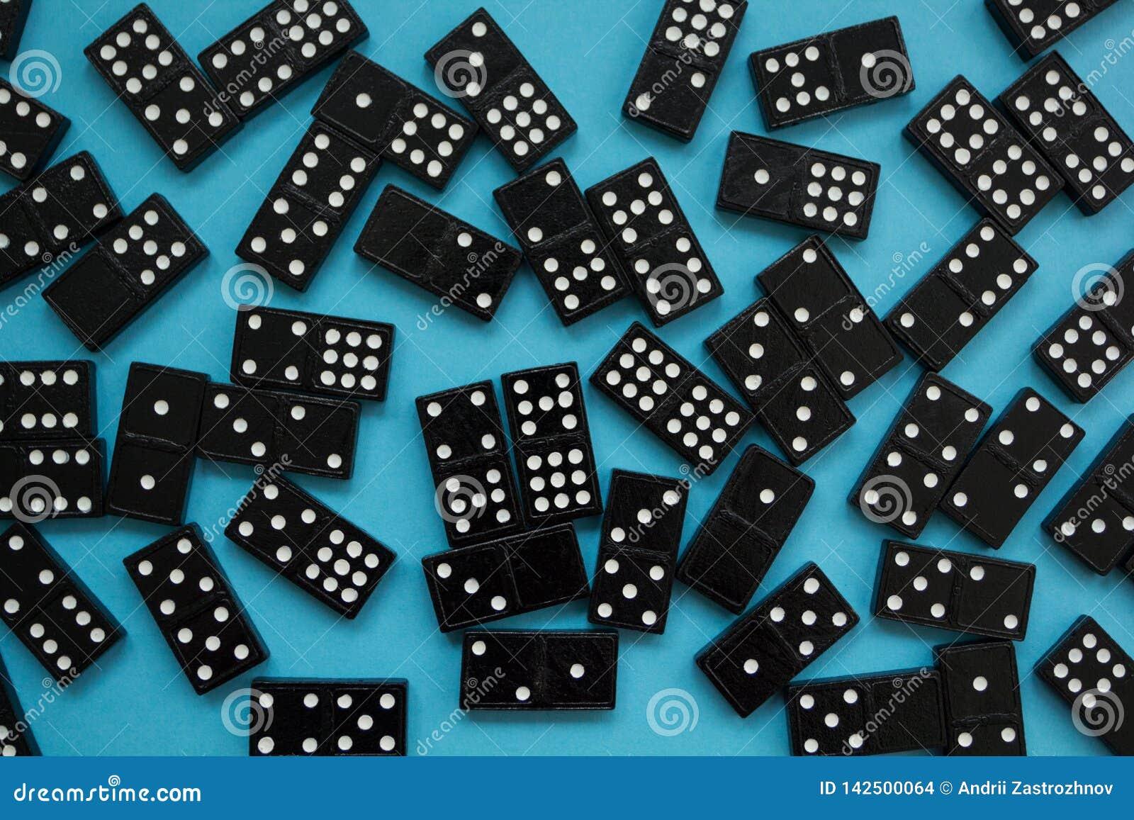 Dominobrickastycken på den blåa bakgrunden