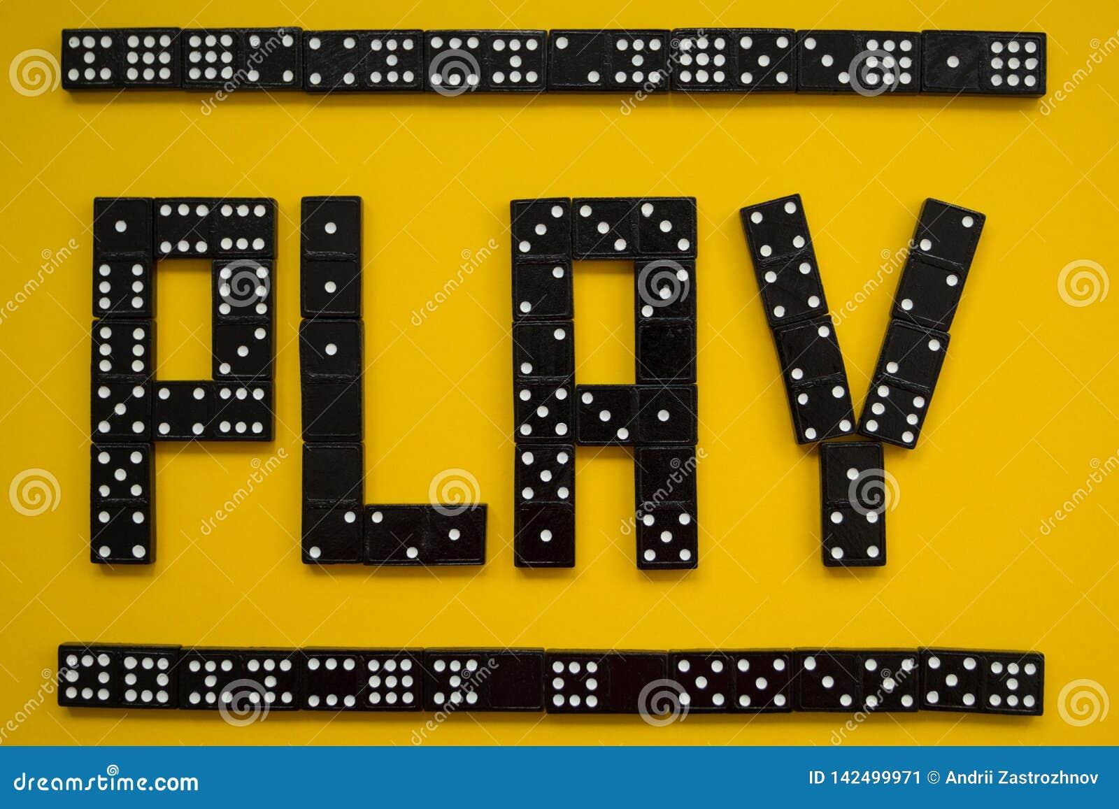 Dominobrickastycken på den gula bakgrunden, lek