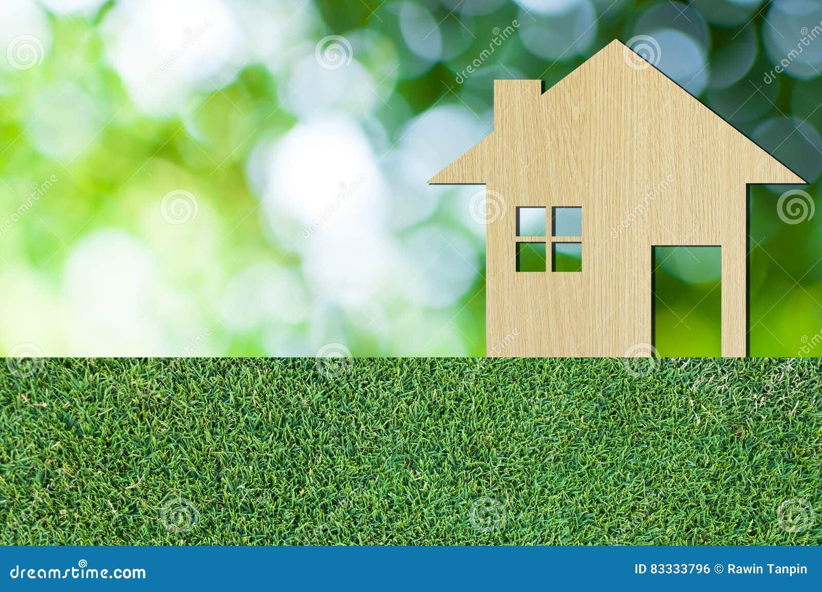 Domowa ikona od drewnianego na trawy tekstury natury tle jako symbol hipoteka