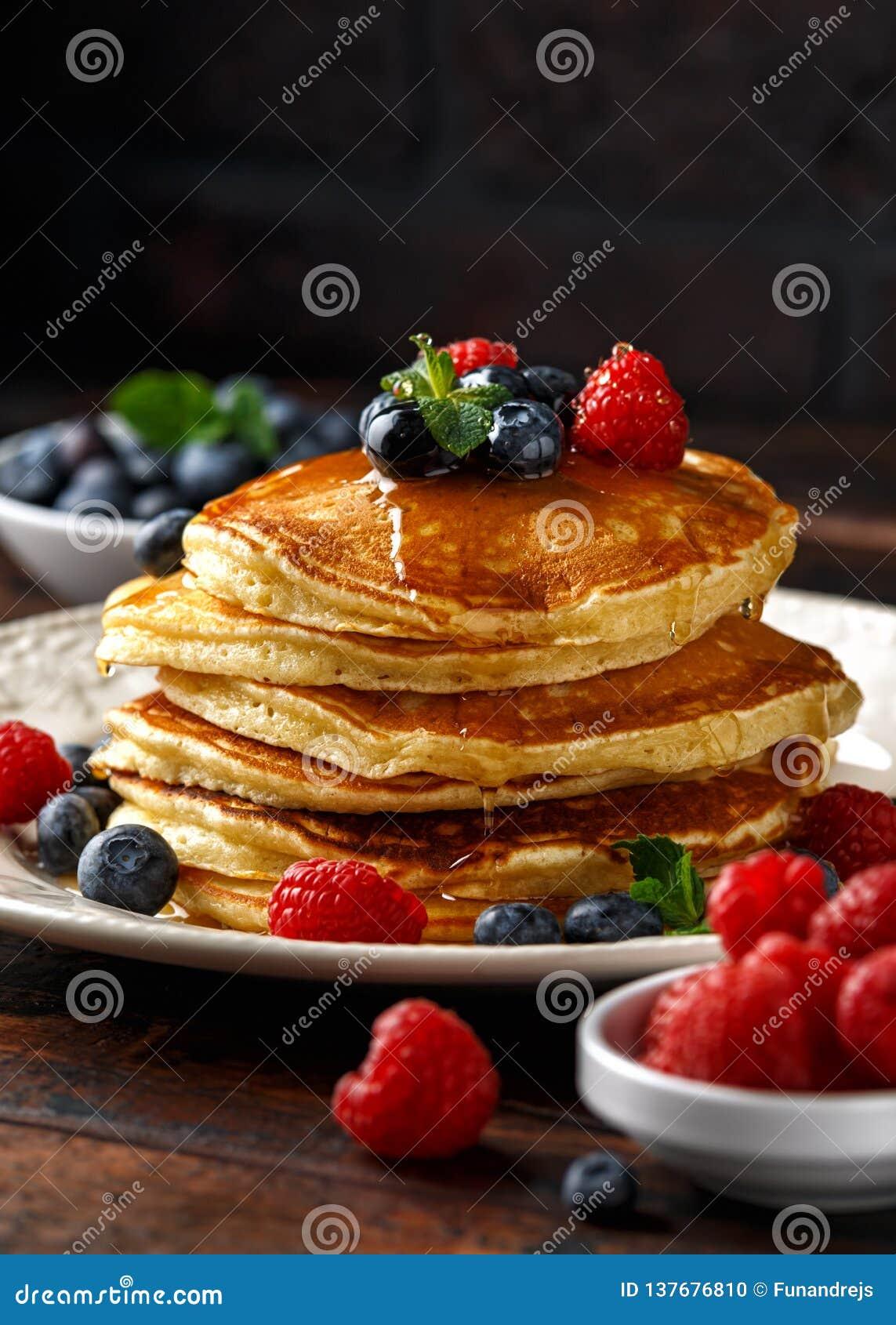 Domowej roboty amerykańscy bliny z świeżą czarną jagodą, malinkami i miodem, Zdrowego ranku wieśniaka śniadaniowy styl