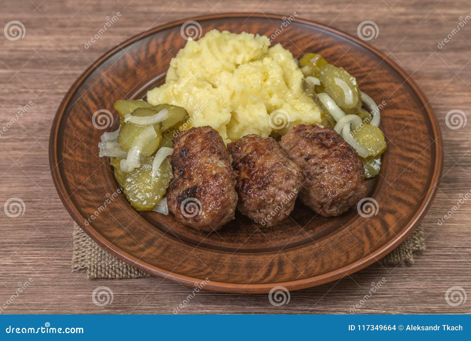 Domowej roboty cutlets mięso z puree ziemniaczane w ceramicznym naczyniu brąz