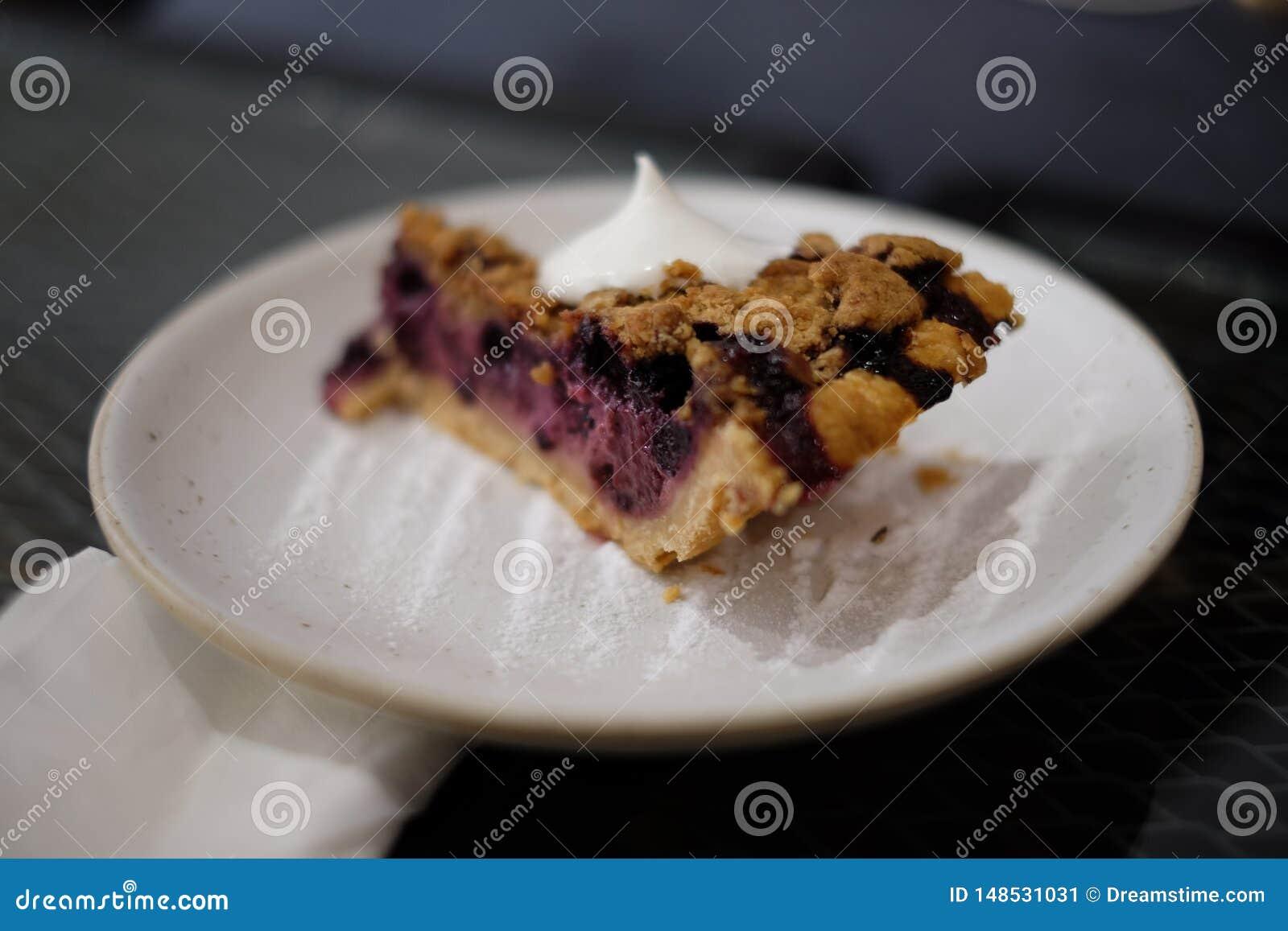 Domowej roboty czarna jagoda kulebiak na talerzu