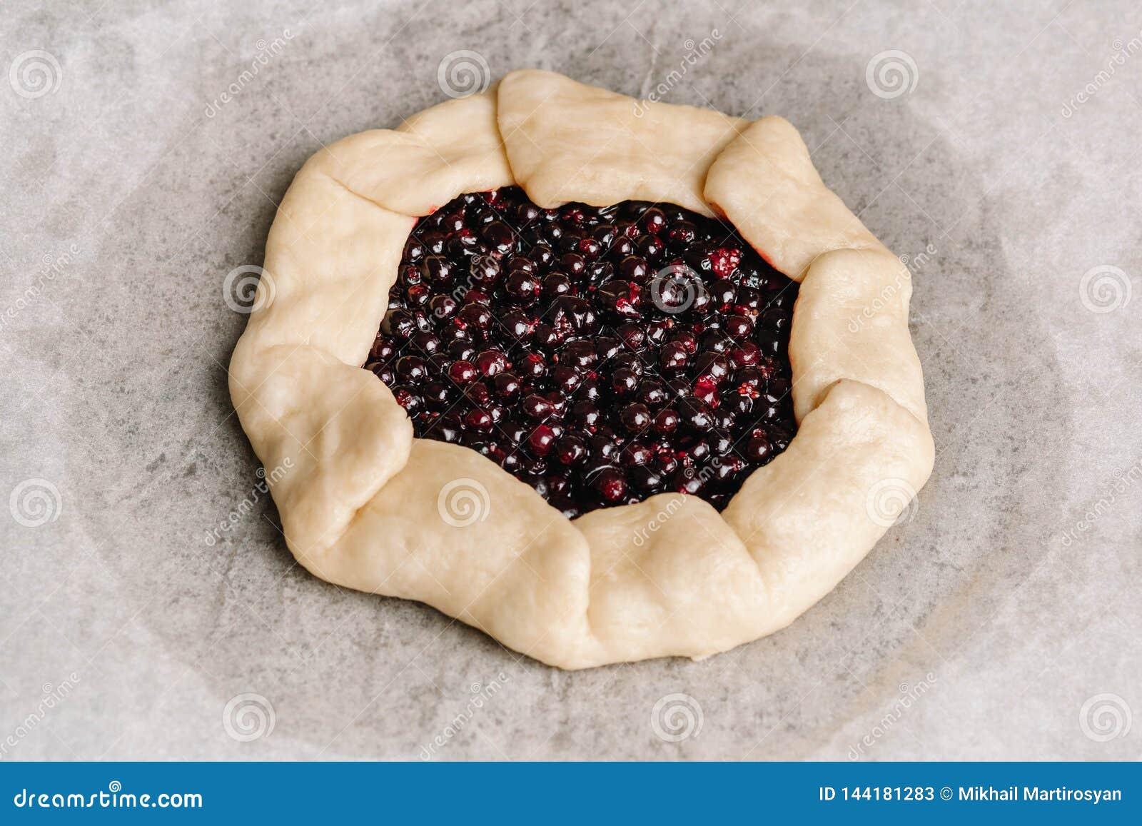 Domowej roboty galette kulebiak z rodzynkami, czarnymi jagodami i malinkami na drewnianym tle czerwonymi i czarnymi,