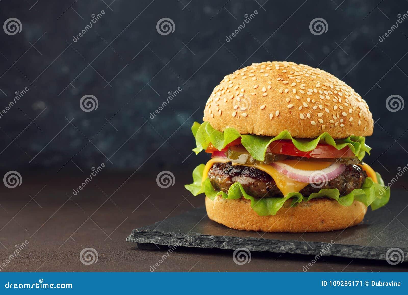 Domowej roboty hamburger z wołowiny cutlet, cheddar, sałata i warzywa na łupku, wsiadamy