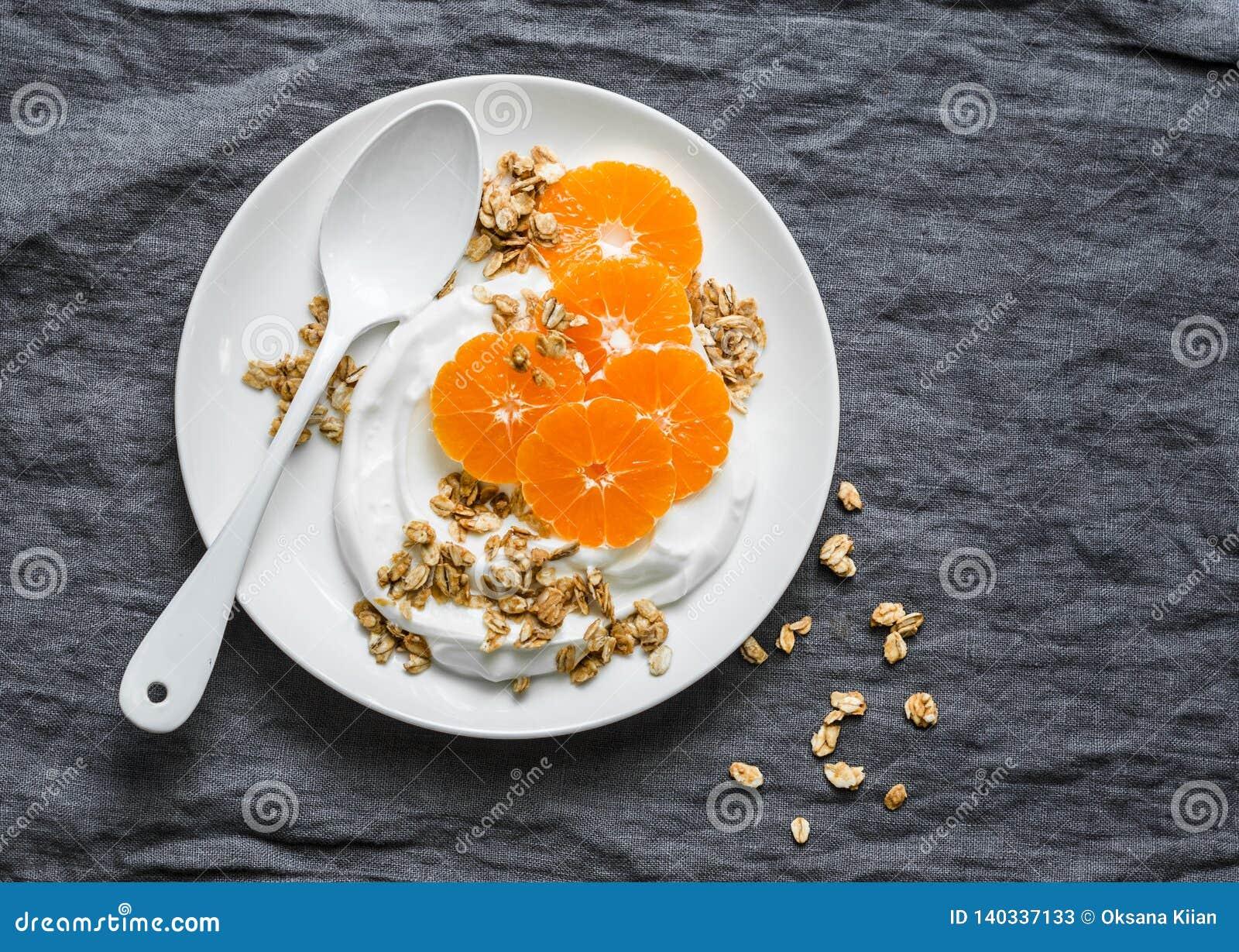 Domowej roboty kokosowy jogurt z granola i tangerines na popielatym tle Gluten uwalnia