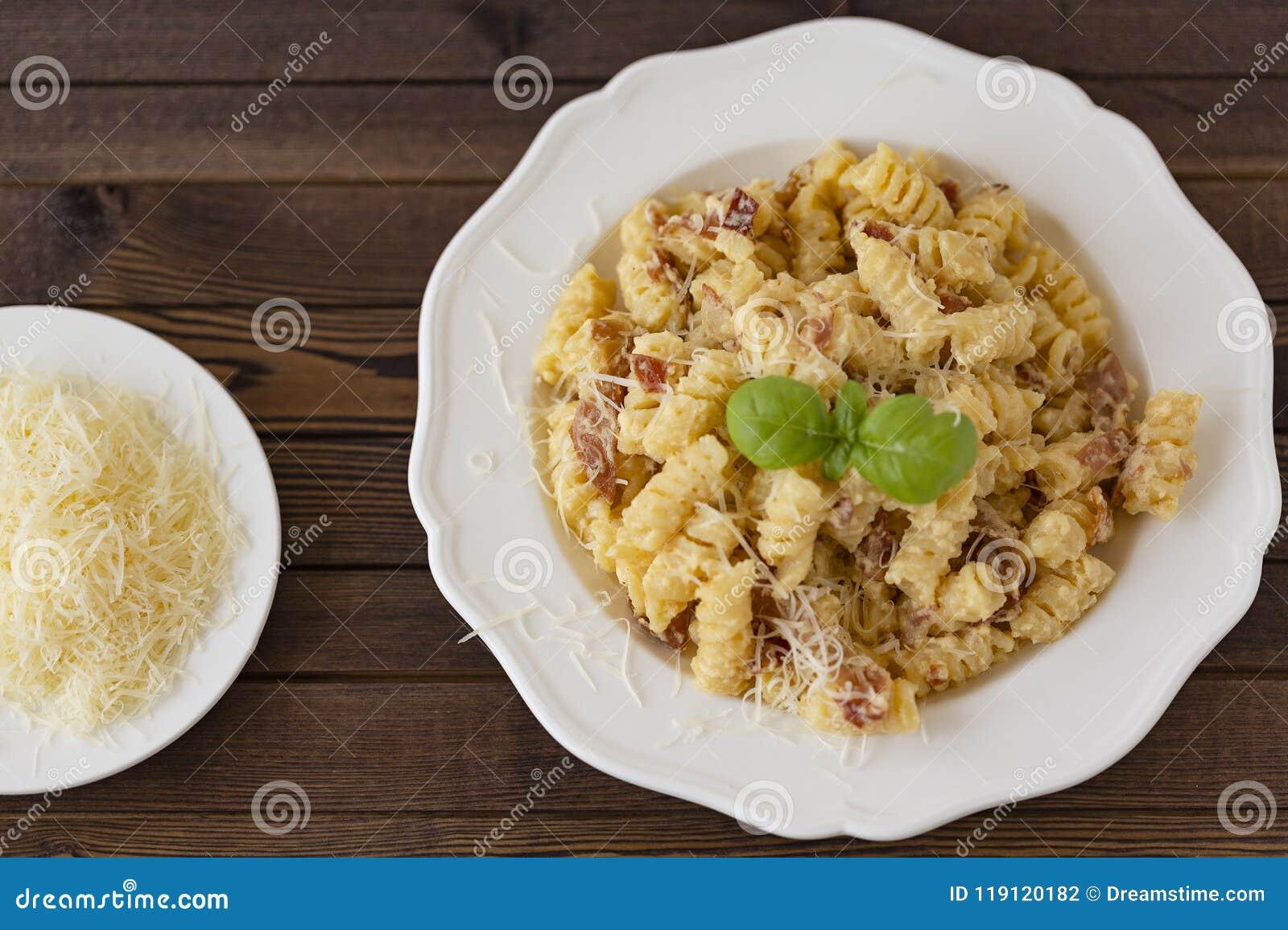 Domowej roboty makaronu carbonara włoszczyzna z bekonem, jajka, Parmezański ser na bielu talerzu na ciemnym tle