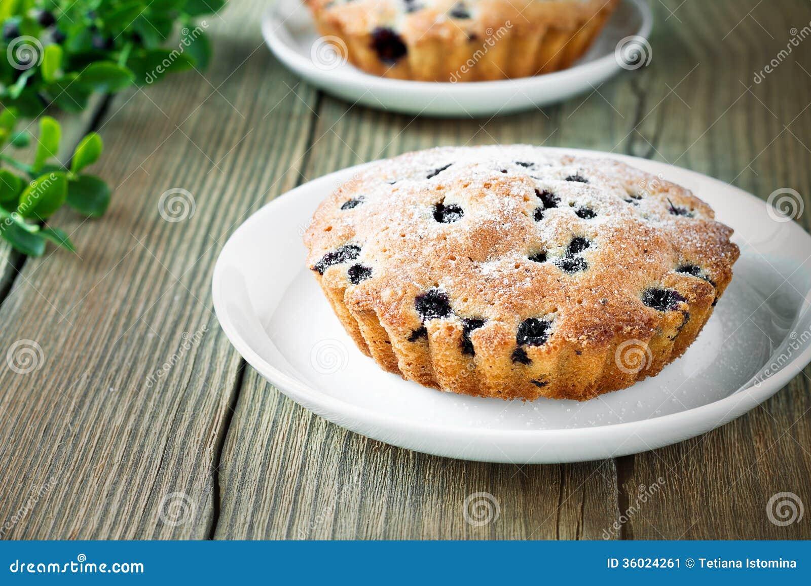 Domowej roboty mini świezi czarna jagoda kulebiaki na bielu talerzu