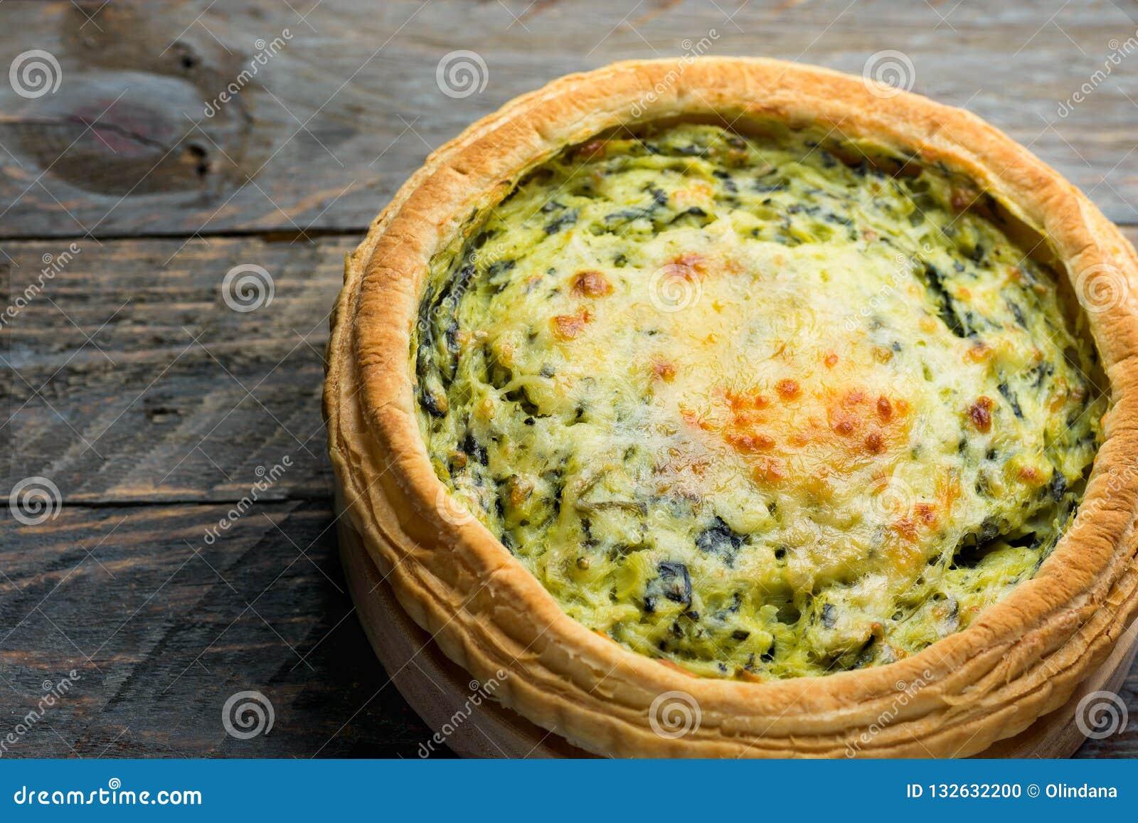 Domowej roboty ptysiowego ciasta quiche Lorraine z leeks szwajcarskim gruyere i miękki koźli ser z klawą złotą skorupą na drewnie