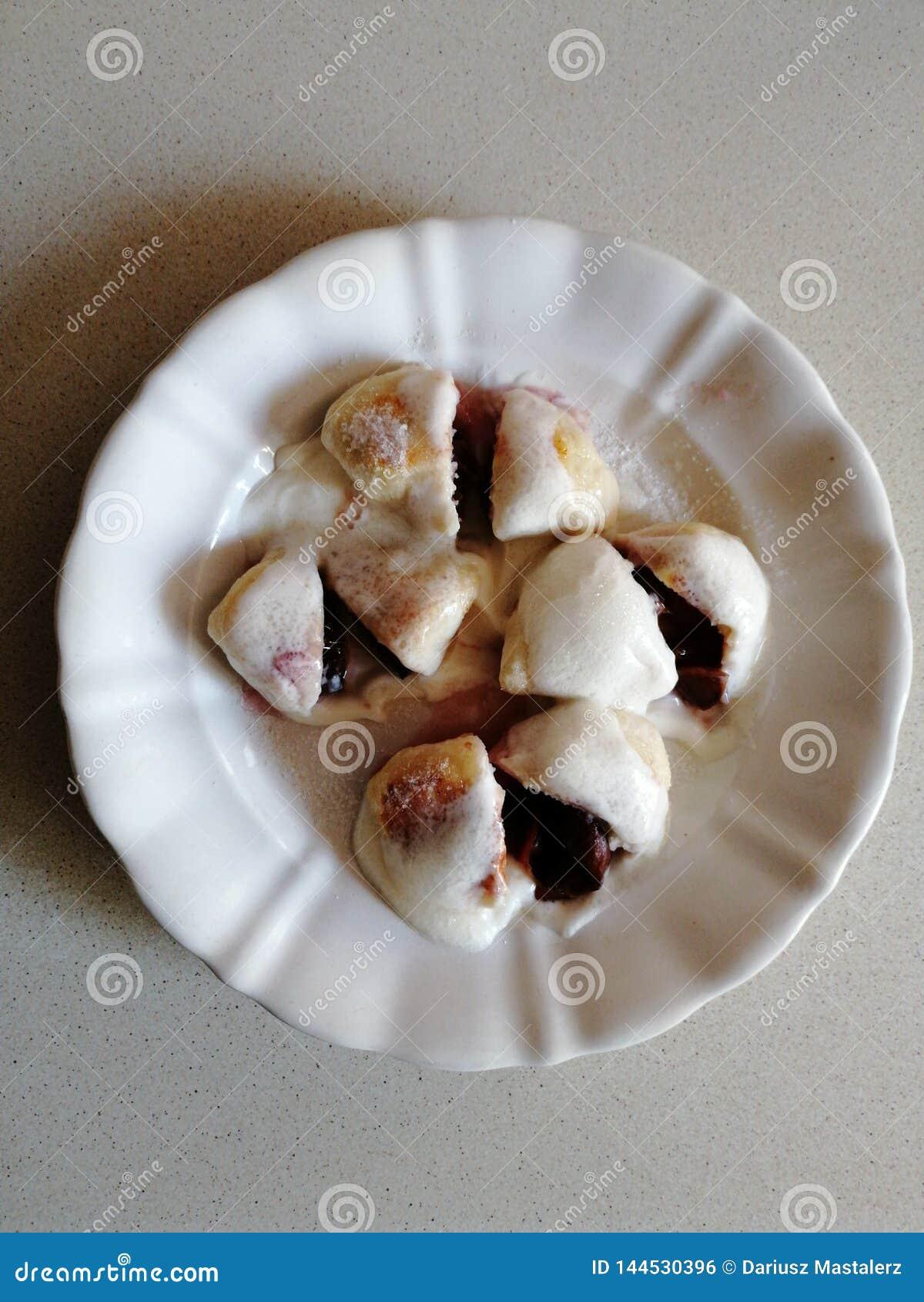 Domowej roboty słodkie śliwkowe kluchy z kwaśną śmietanką 2 i cukierem