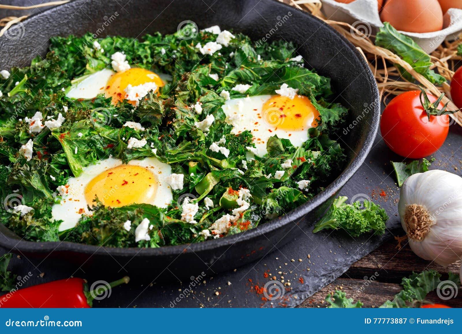 Domowej roboty Zielony Kale z jajkami, feta ser, ziele w żelaznej niecce zdrowy nieociosany śniadanie