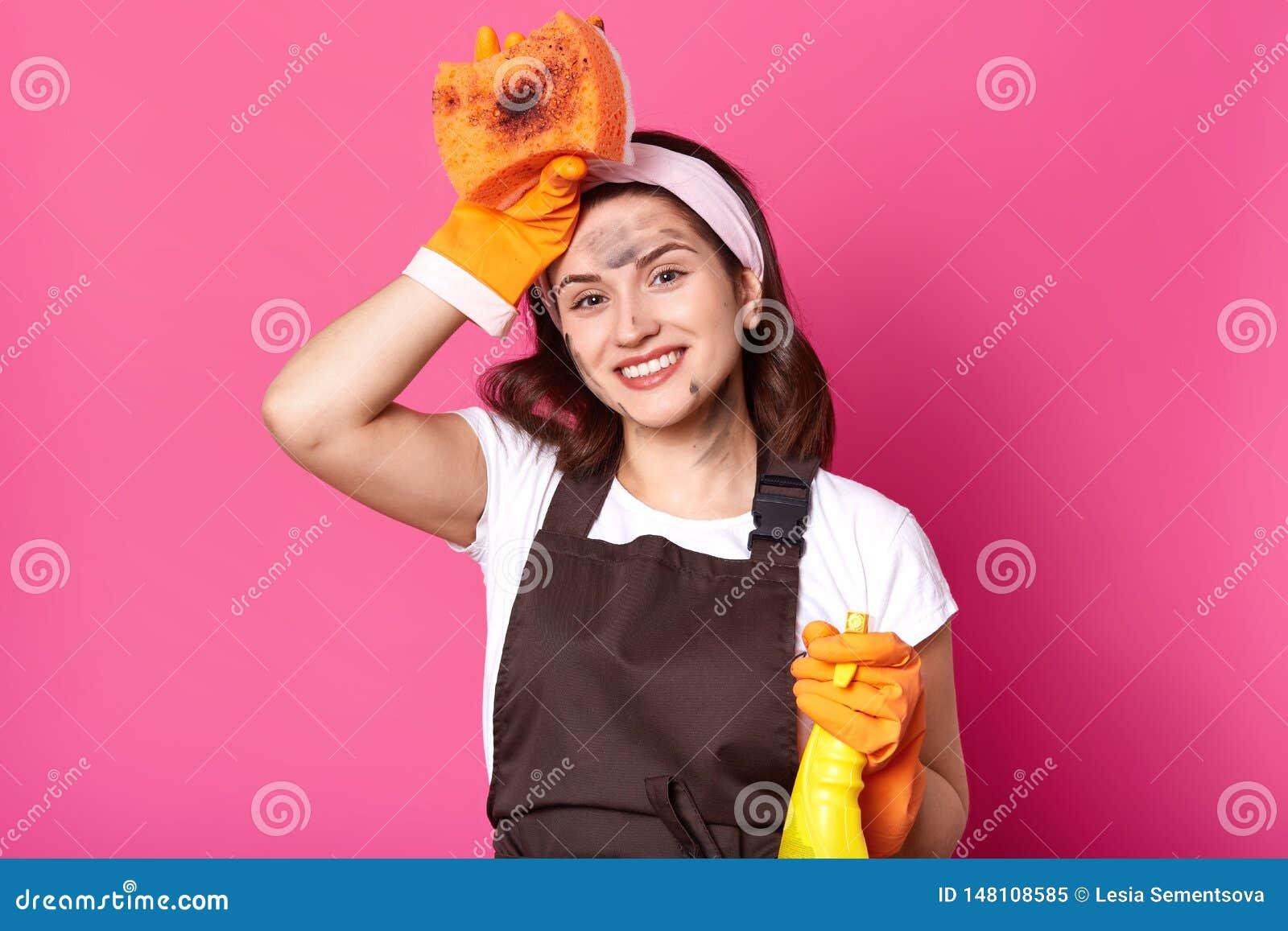 Dona de casa bonita que levanta com a mão que toca na cabeça, detergente da terra arrendada, sorrindo sinceramente, tendo a expre