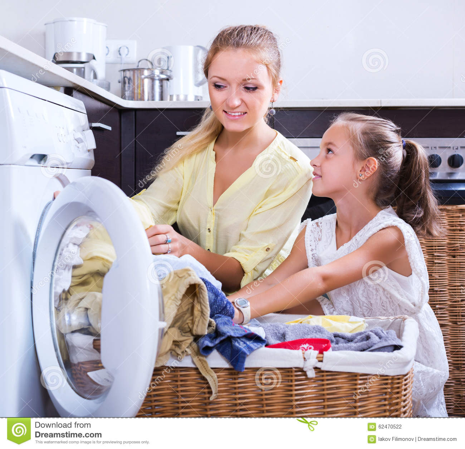 Dona de casa e menina que fazem a lavanderia