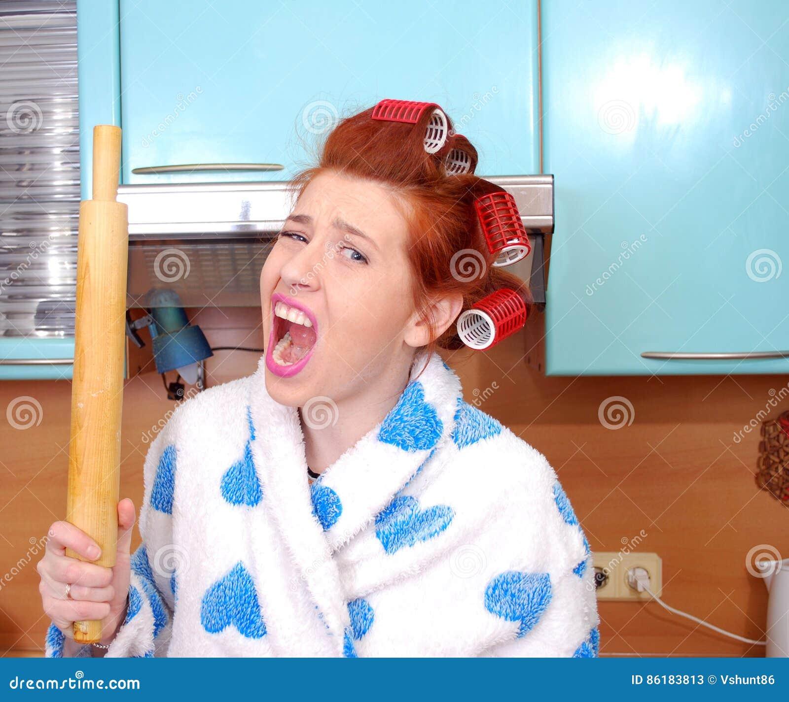 A dona de casa nova em encrespadores de cabelo em gritos da raiva e ameaça a ameaça de um pino do rolo