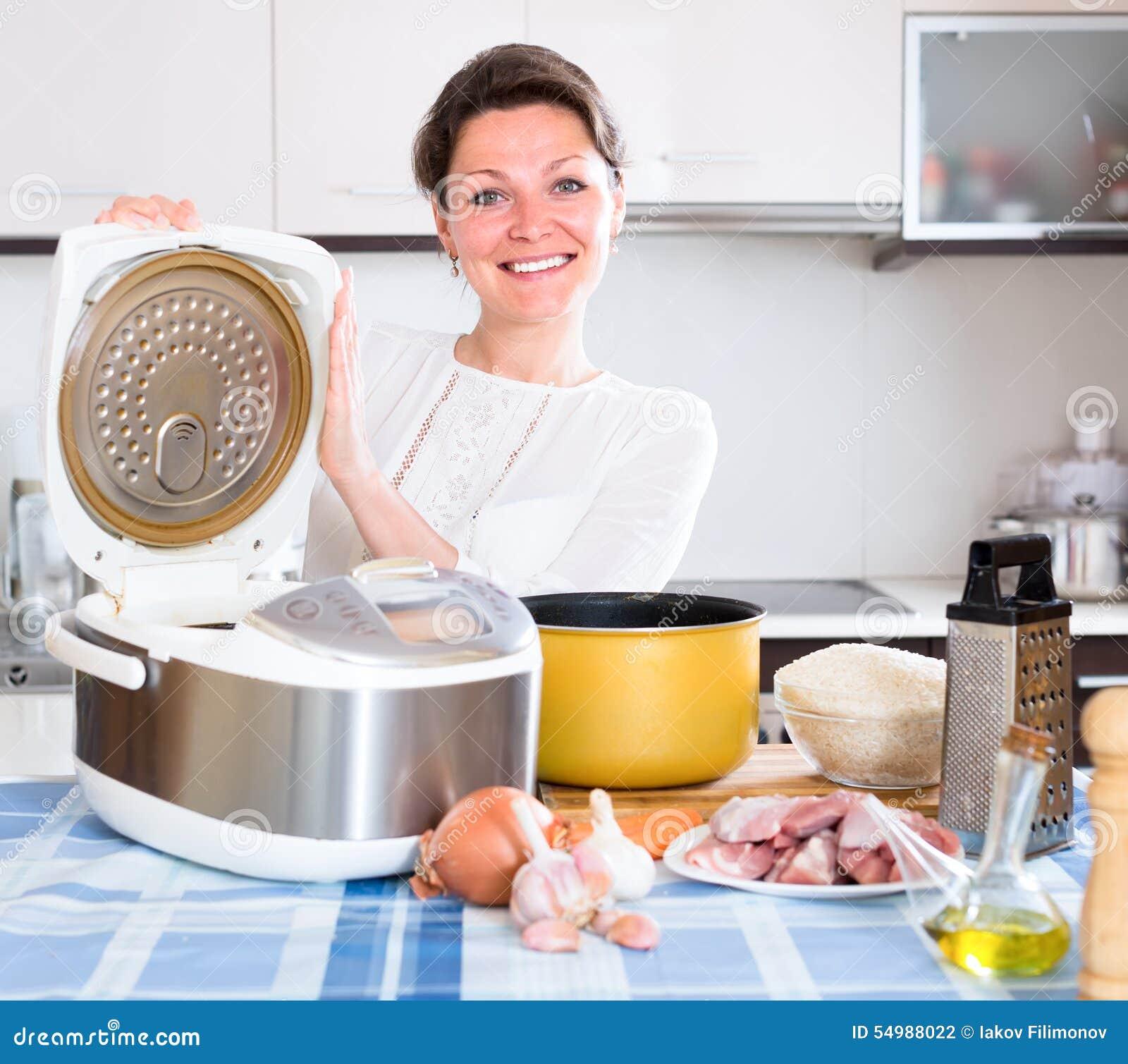 Dona de casa que cozinha o arroz no multicooker
