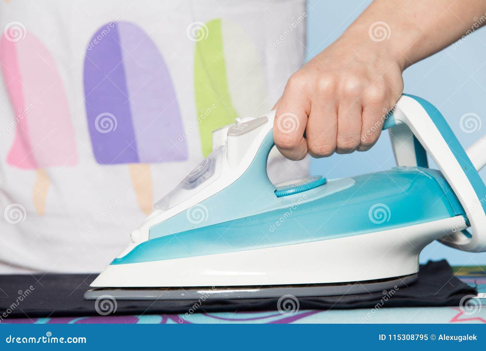 Dona de casa que faz trabalhos domésticos Opinião do close-up do ferro moderno na mão da mulher