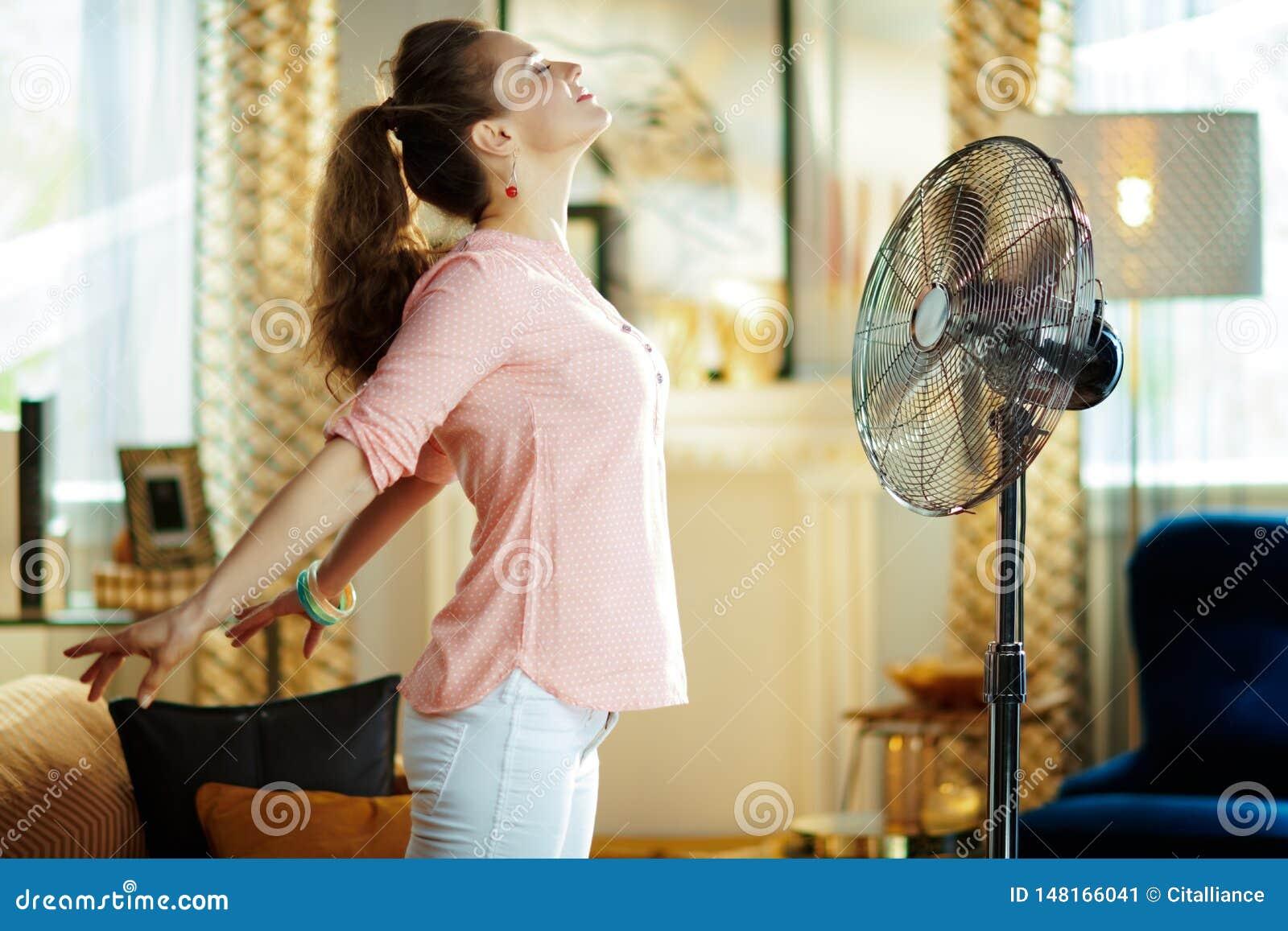 Dona de casa relaxado que aprecia o frescor na frente do f? de trabalho