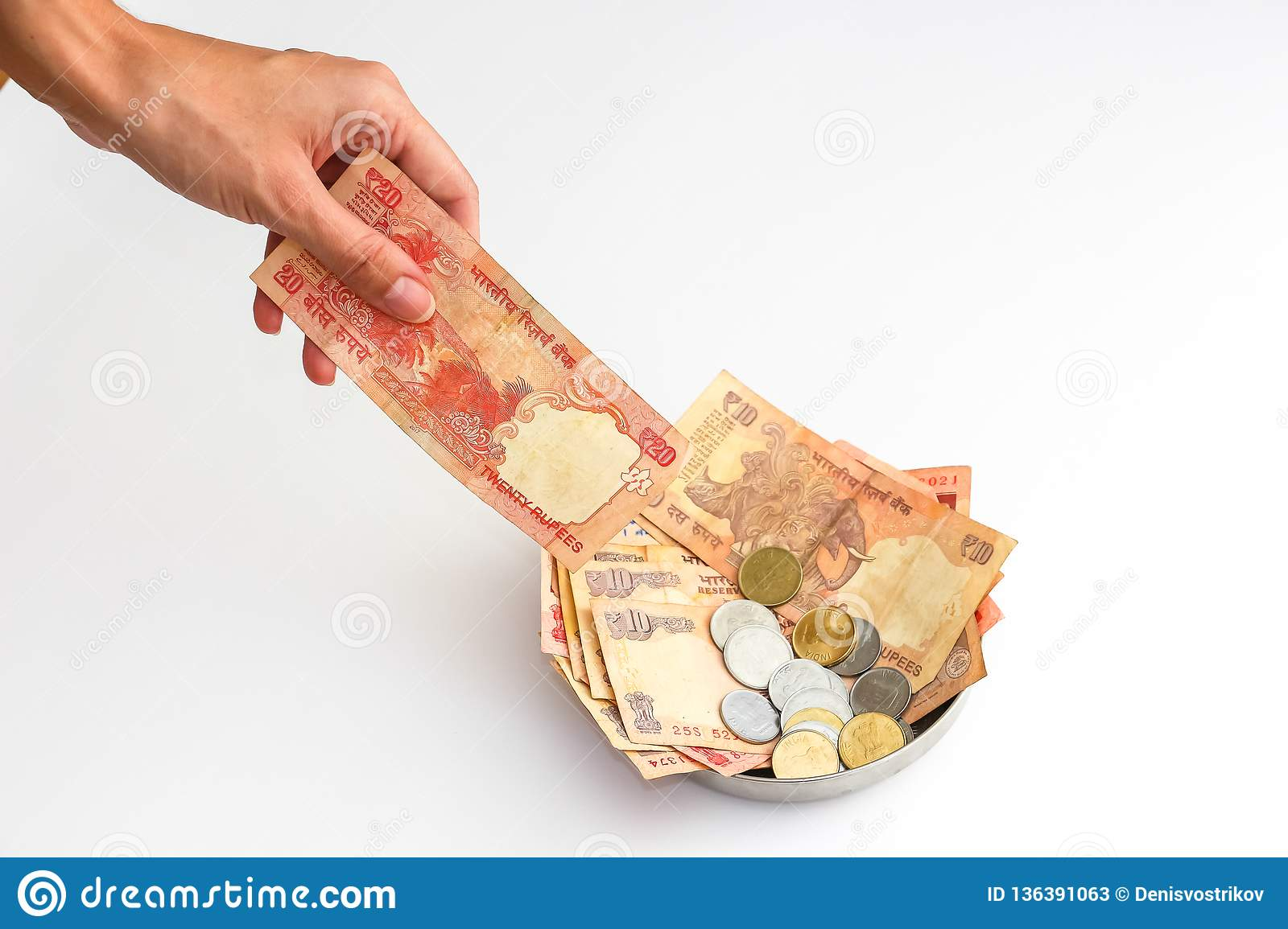 Donation plate with indian banknotes and coins on white background