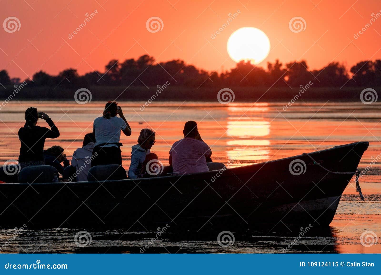 Donaudelta, Rumänien, Augusti 2017: turister som håller ögonen på solnedgången