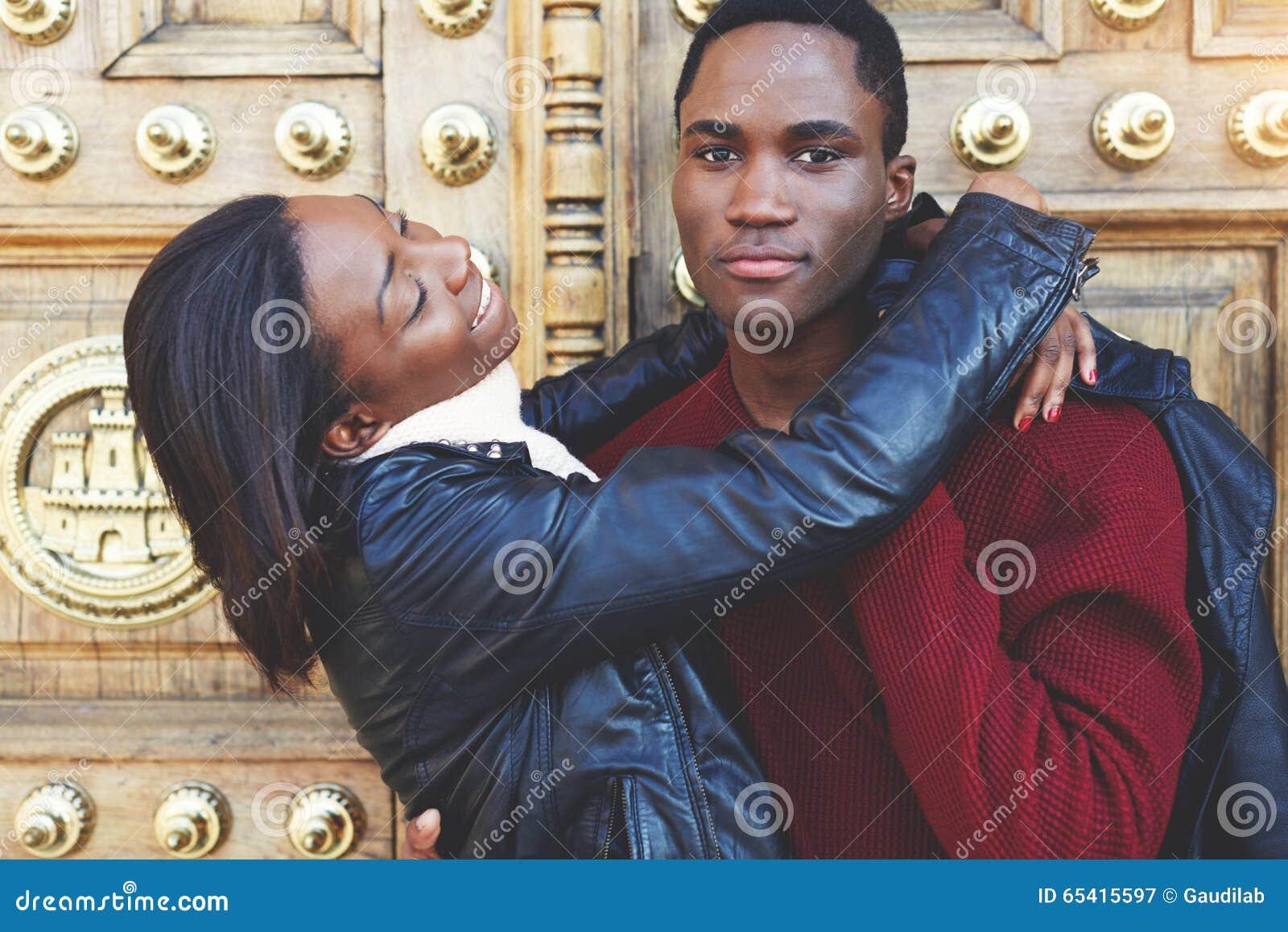 Donker gevild paar die pret hebben terwijl status in openlucht tegen uitstekende deur, twee vrienden die recreatie van tijd genie
