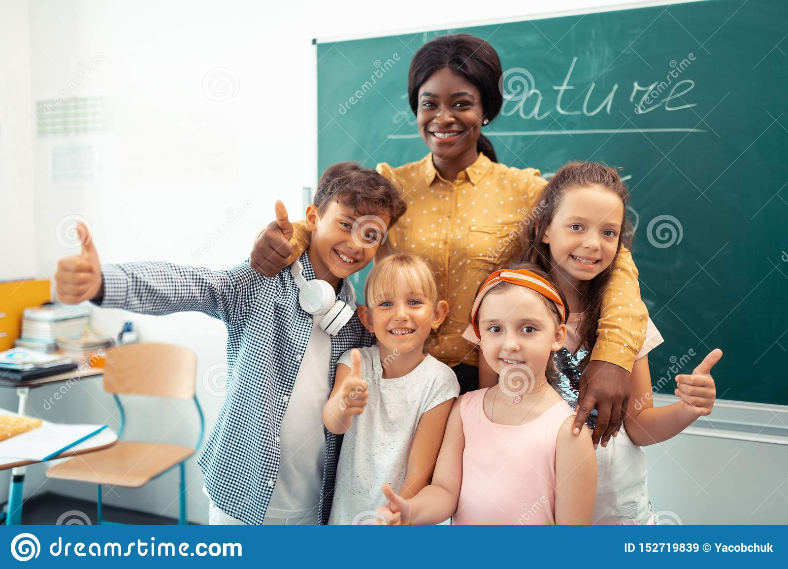 Donker-gevilde leraar die vrolijk met haar grappige slimme leerlingen voelen