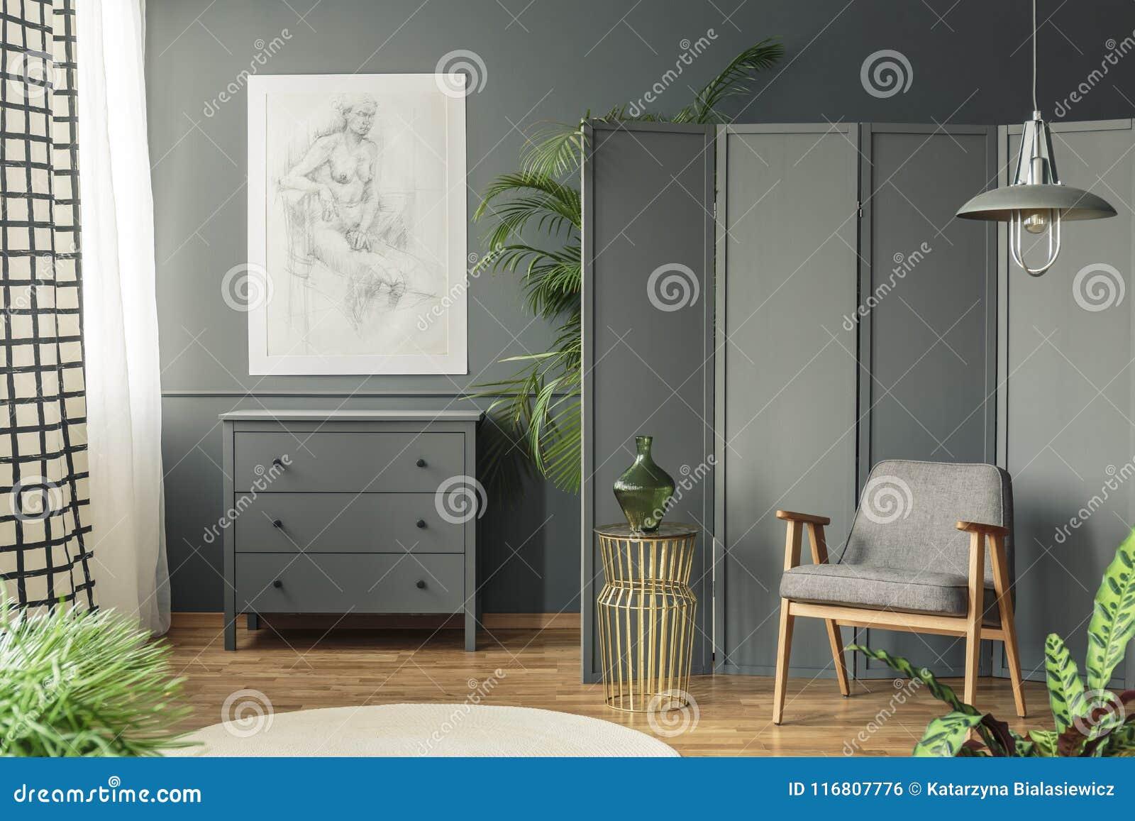 Donker, grijs woonkamerbinnenland met een schets die boven een wo hangen