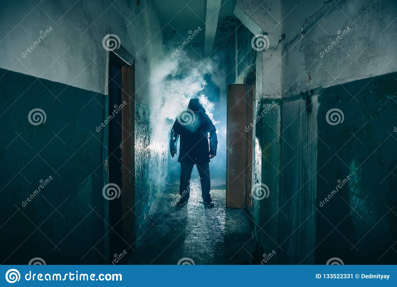 Donker silhouet van de vreemde gevaarsmens in kap in achterlicht met rook of mist in enge grungegang of tunnel