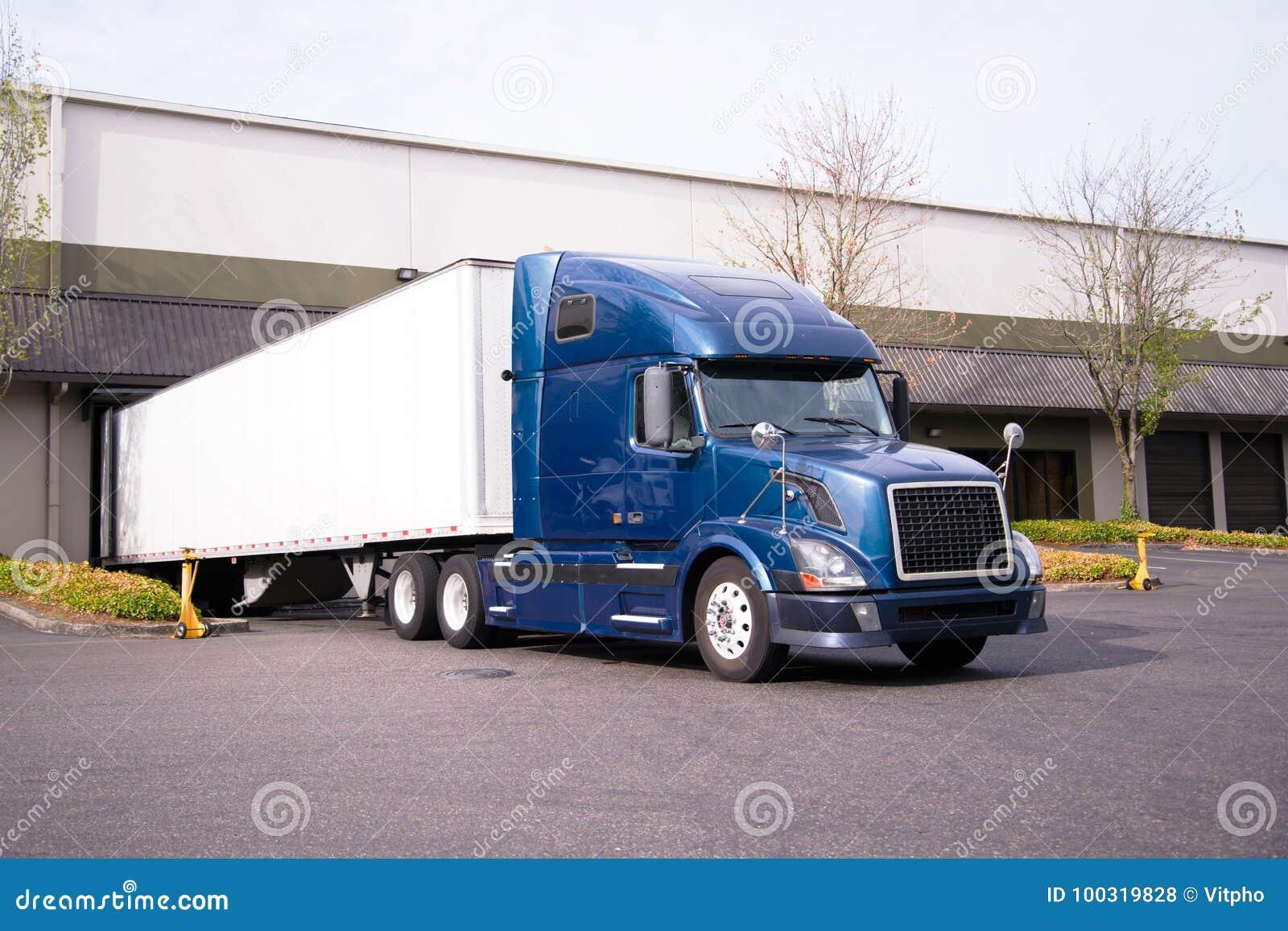 Donkerblauwe grote installatie semi vrachtwagen met aanhangwagen in de lading van het pakhuisdok