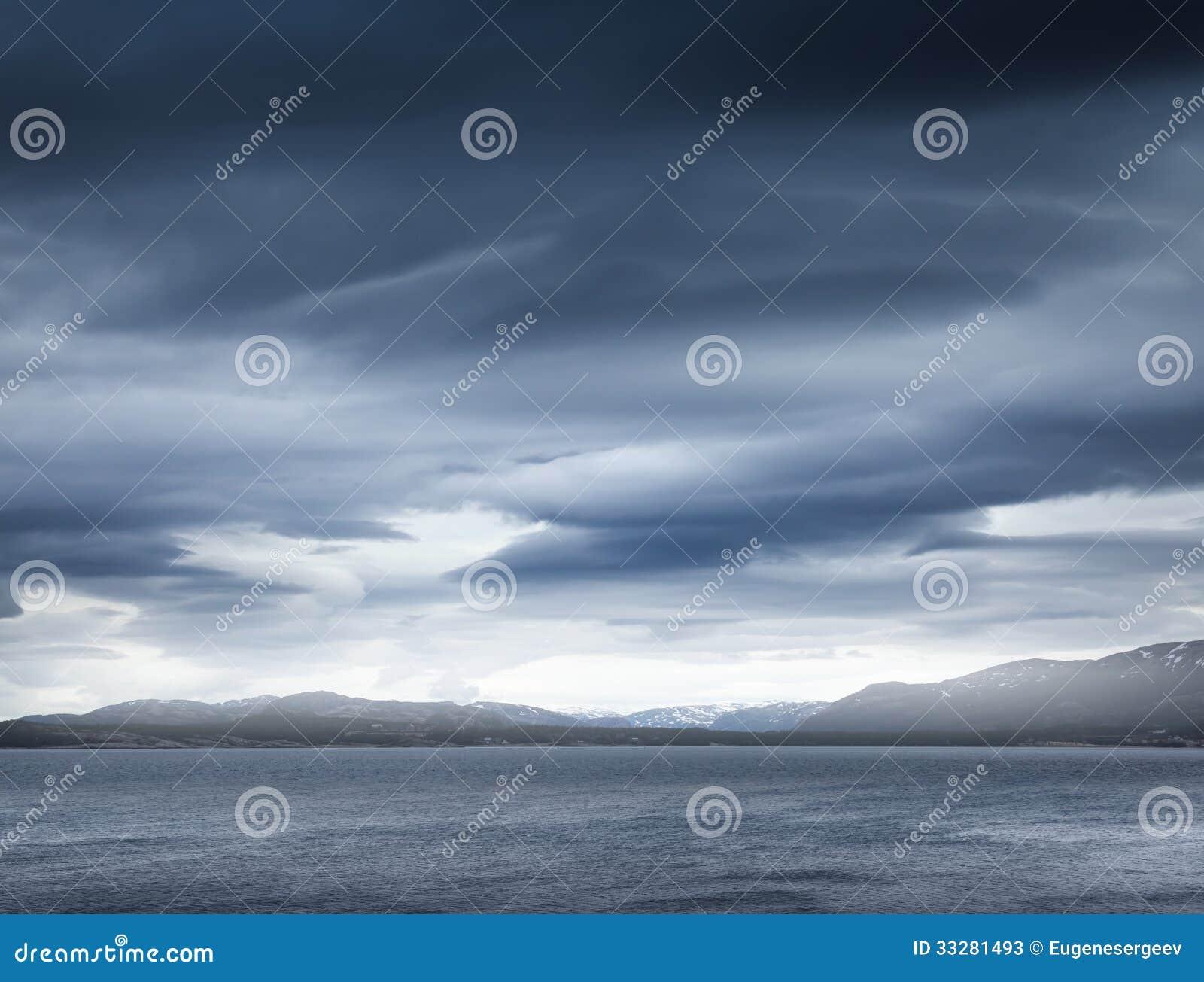 Donkerblauwe stormachtige wolken over de kustrotsen