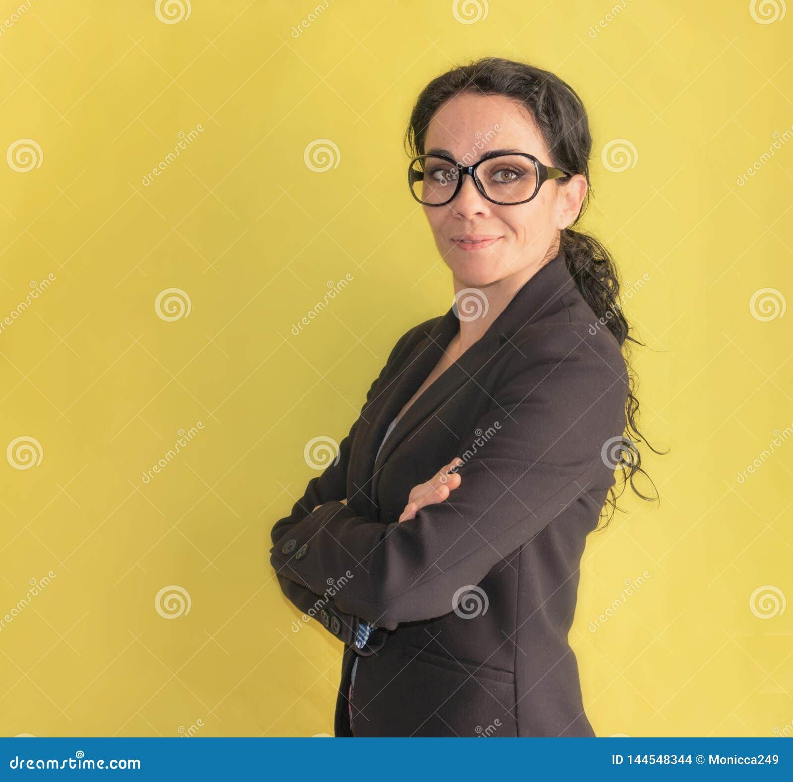 Donkerbruine bedrijfsvrouw die met glazen bij de camera glimlachen