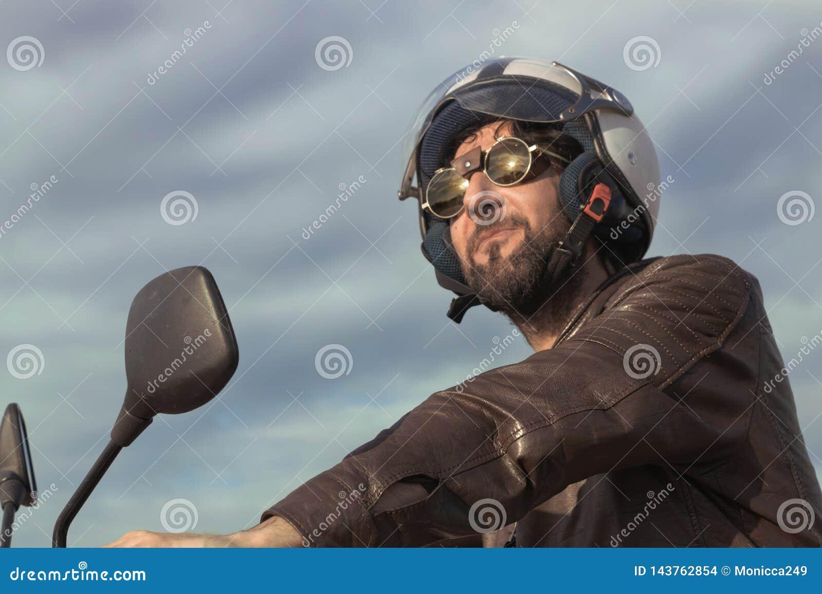 Donkerbruine mens met bruin leerjasje op een motor
