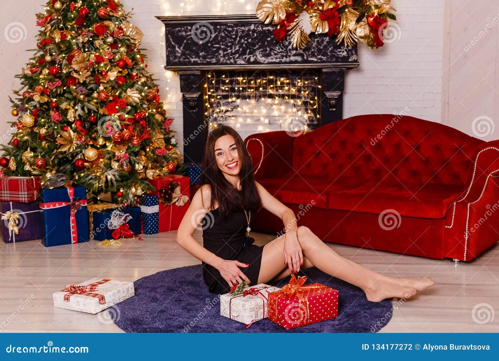 Donkerbruine vrouw in plotseling zwarte kledingszitting op het tapijt dichtbij de Kerstboom Lachende jonge vrouw Mooi wijfje