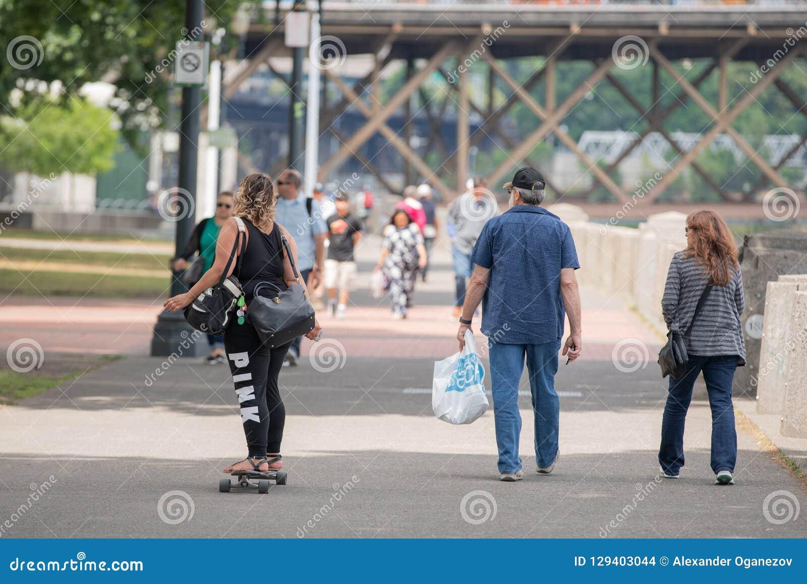 Donkere gevilde vrouw met twee zakken die een skateboard berijden