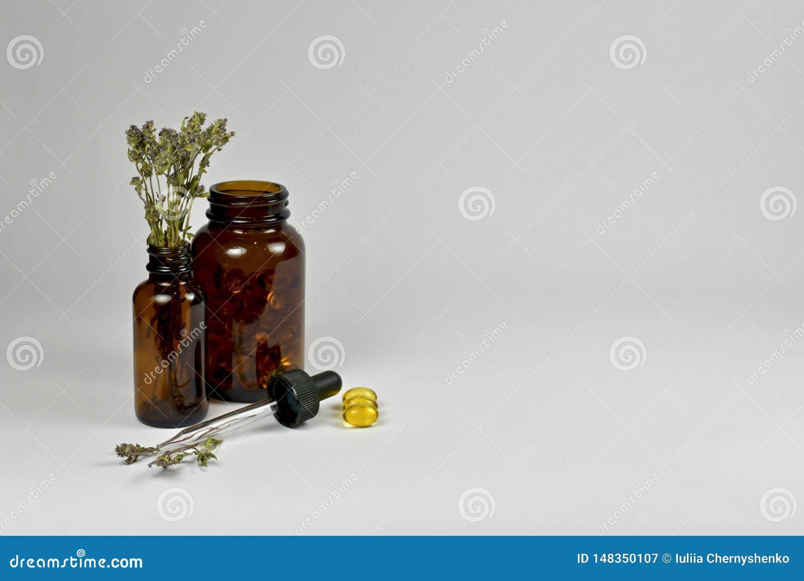 Donkere glas medische flessen, droge thyme, oliecapsules en een GLB-pipet