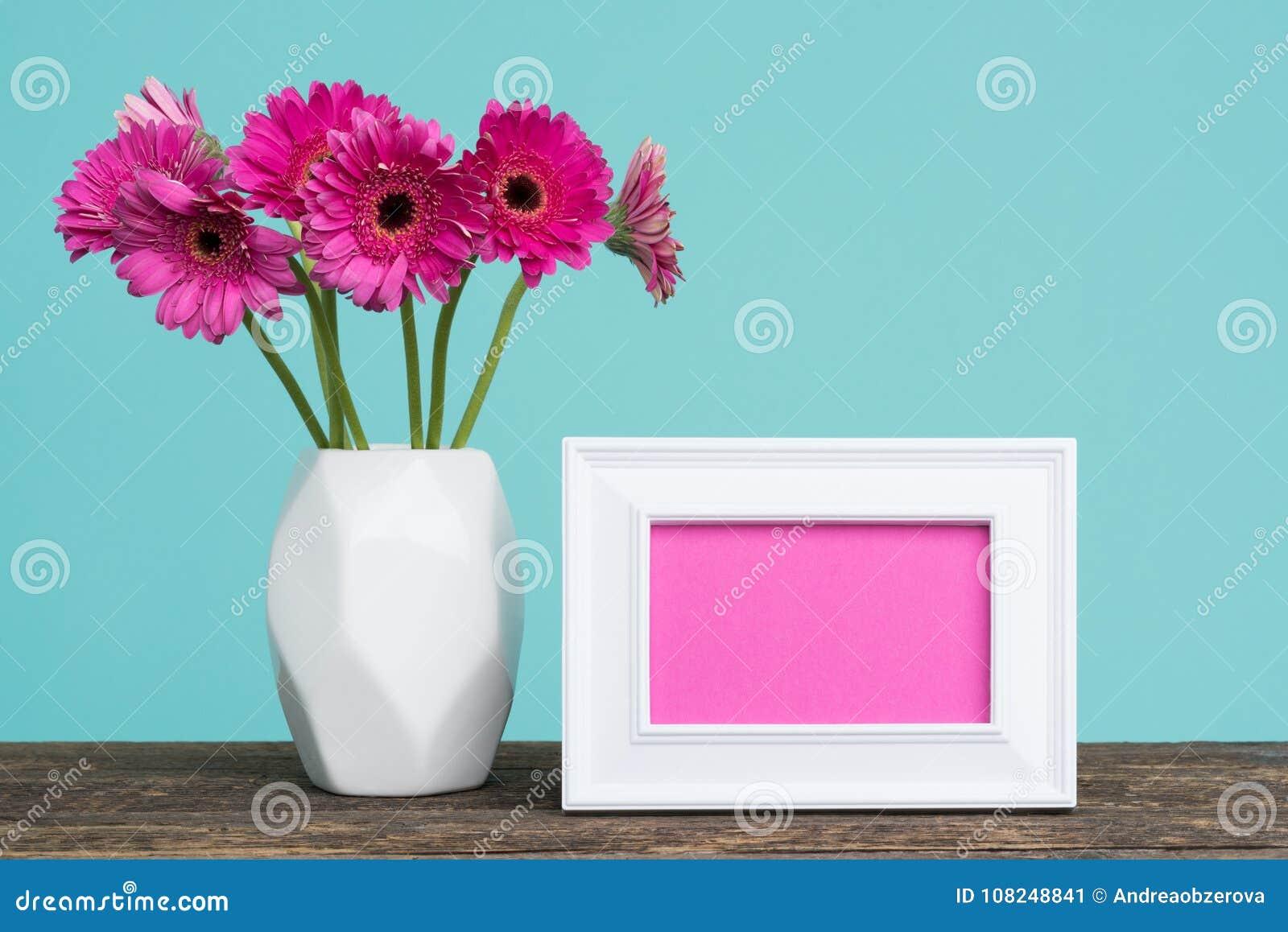 Donkere roze gerberas in een vaas op een lijst met de lege kaart van de omlijstinggroet