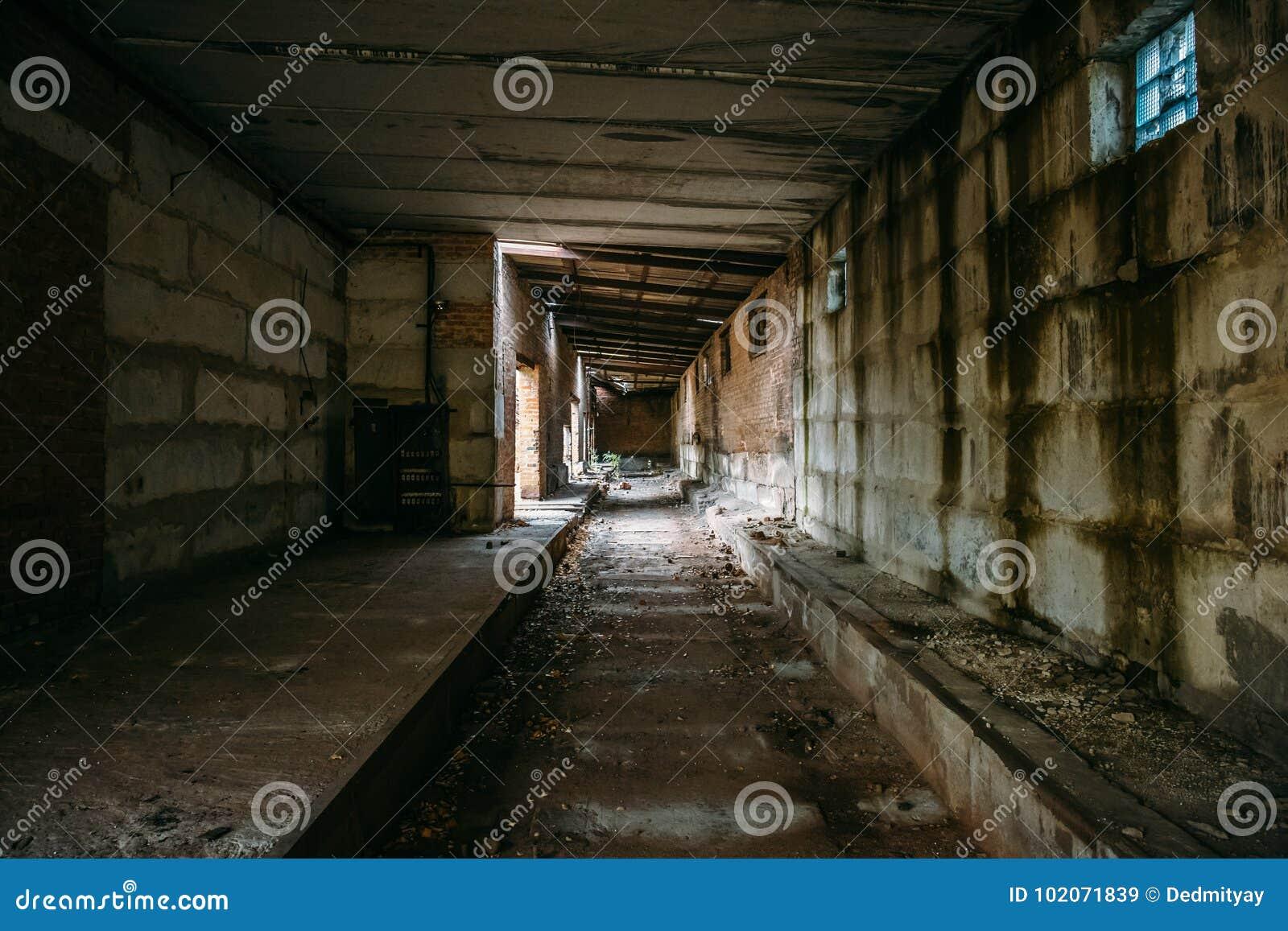 Donkere tunnel in oude verlaten baksteenfabriek Verlaten industriële gang