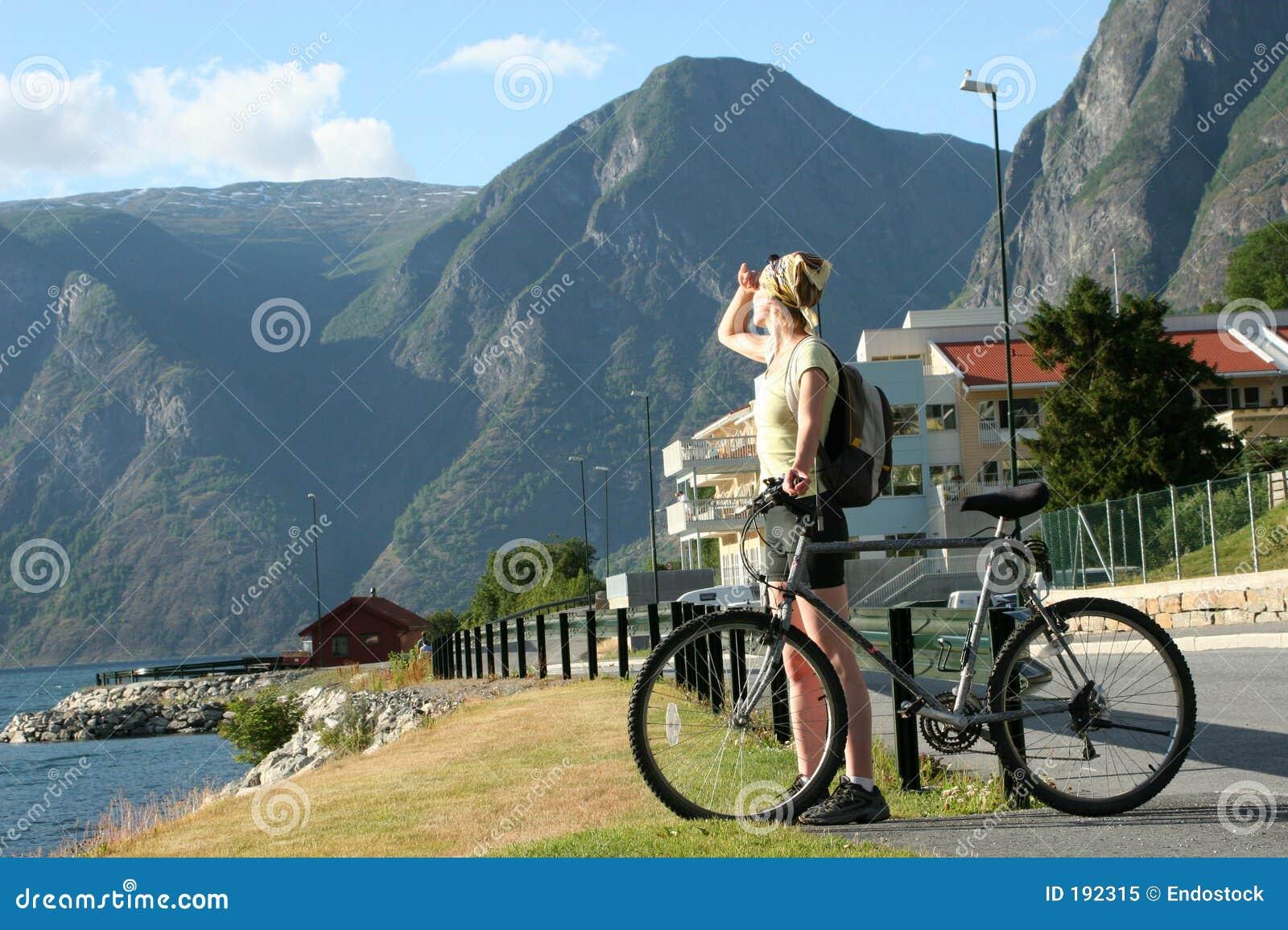 Donna adulta con la bici che esamina le montagne