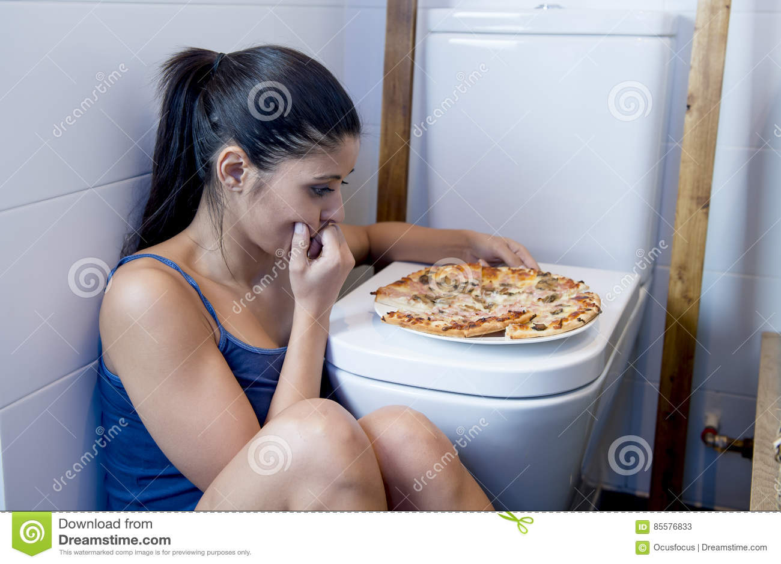 Donna affetta da bulimia che ritiene seduta colpevole malata al pavimento della toilette che si appoggia WC che mangia pizza