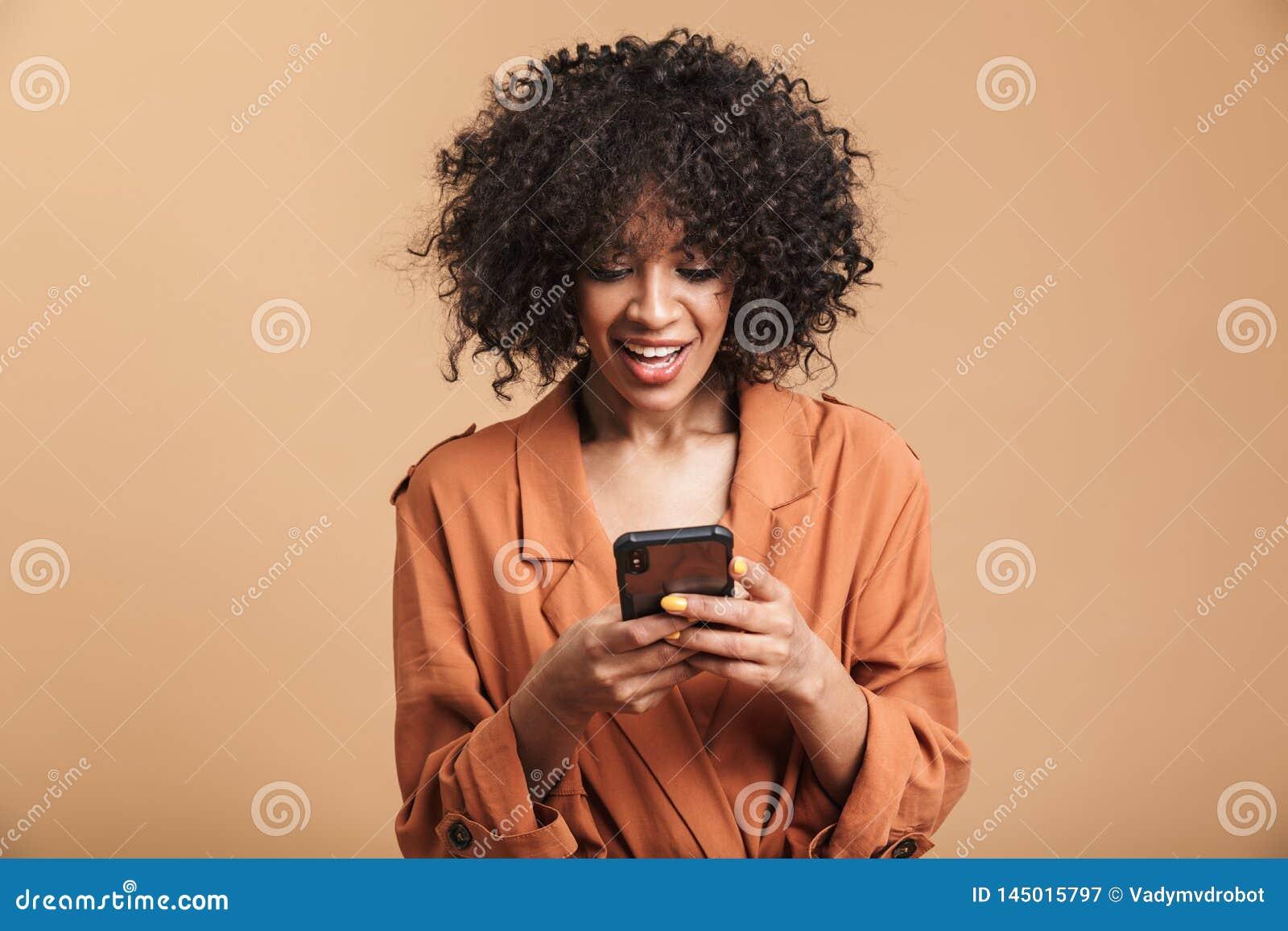 Donna africana graziosa sorridente che scrive messaggio sullo smartphone