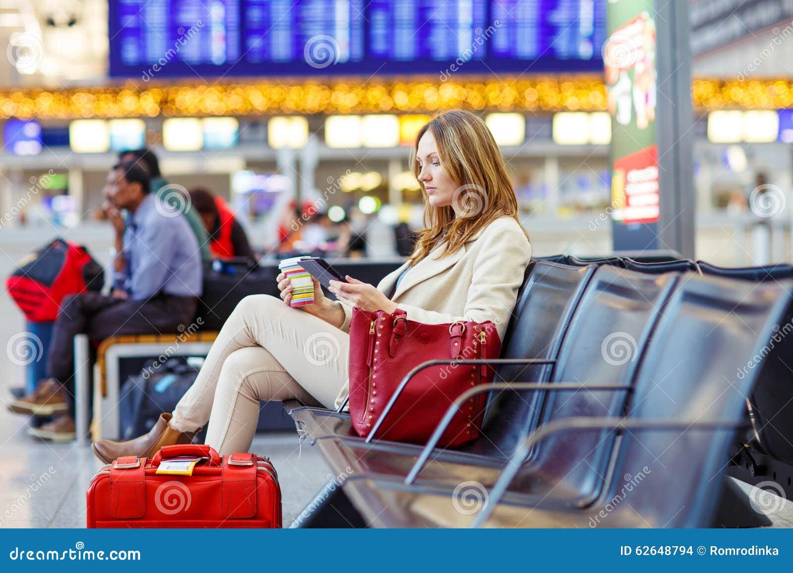 Donna al volo aspettante dell aeroporto internazionale