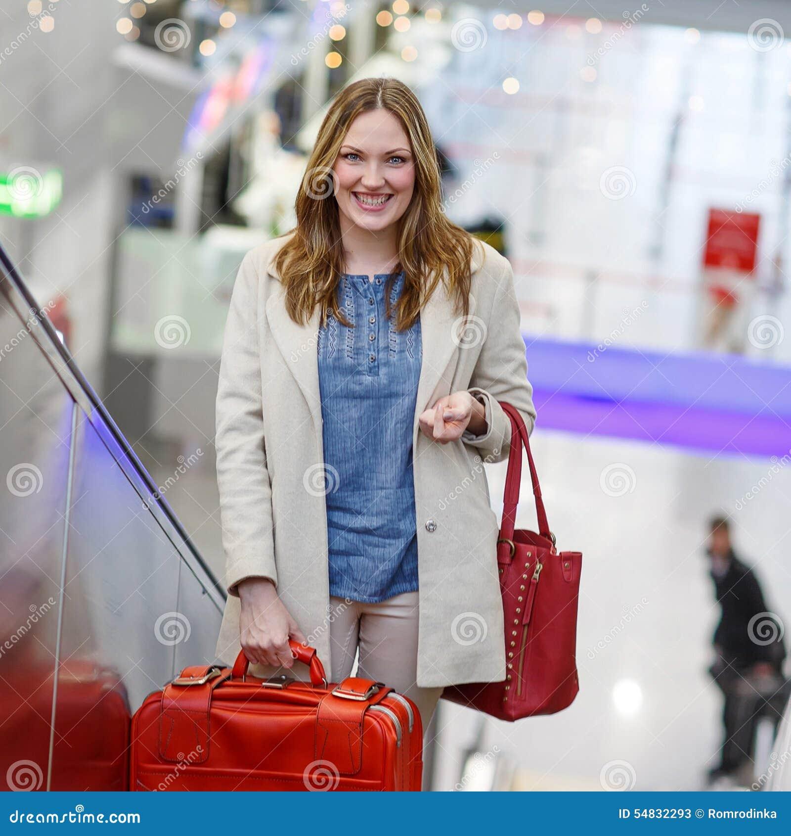 Donna all aeroporto internazionale, sulla scala mobile al terminale di arrivo