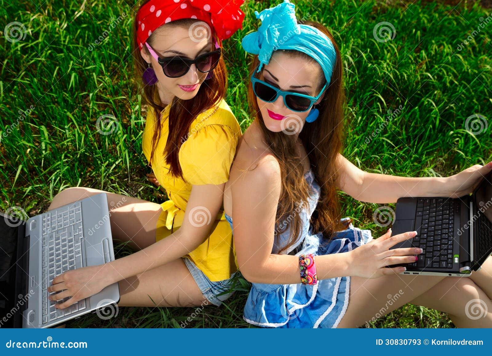 Donna alla moda che per mezzo dei computer portatili