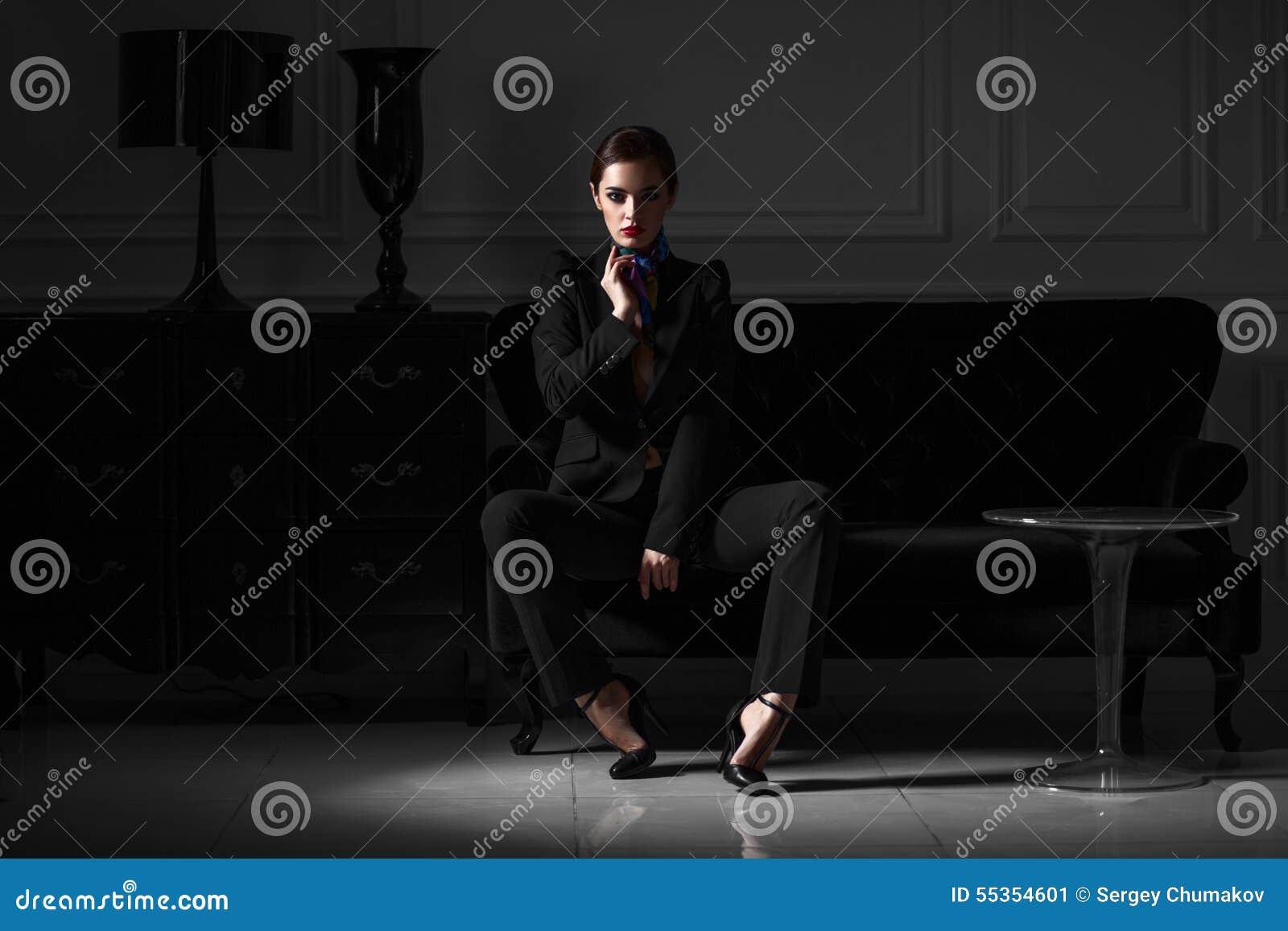 Donna alla moda in vestito nero nell interno minimalistic scuro