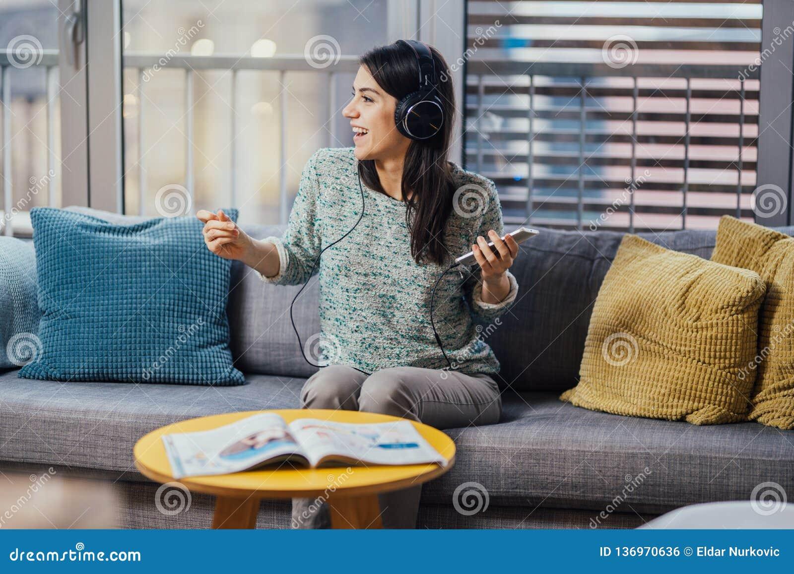 Donna allegra che ascolta la musica con le grandi cuffie e che canta Godendo dell ascoltare la musica a tempo il tempo libero a c