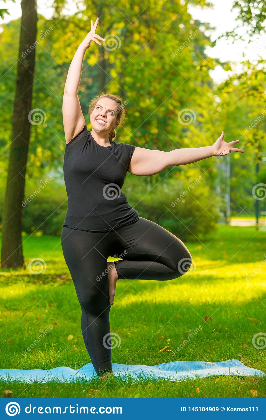 Donna allegra grassa che fa yoga nel parco
