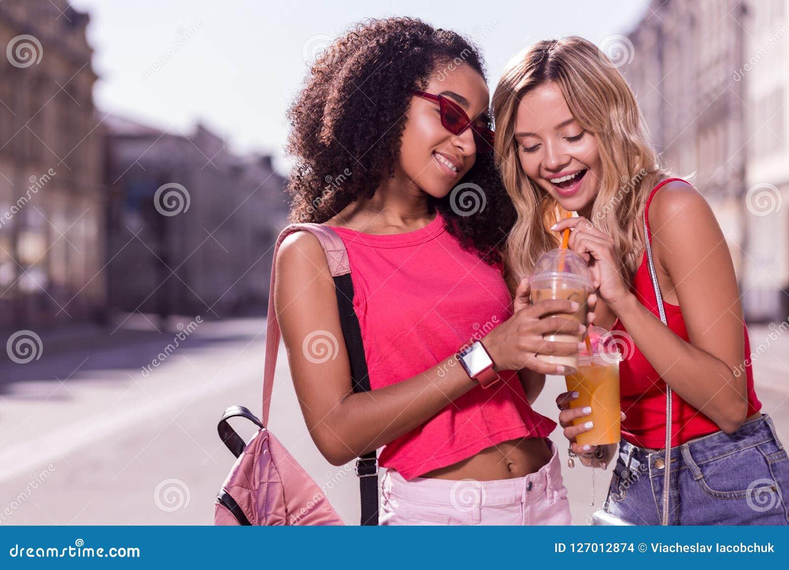 Donna allegra piacevole che prova la sua bevanda degli amici Immagini Stock