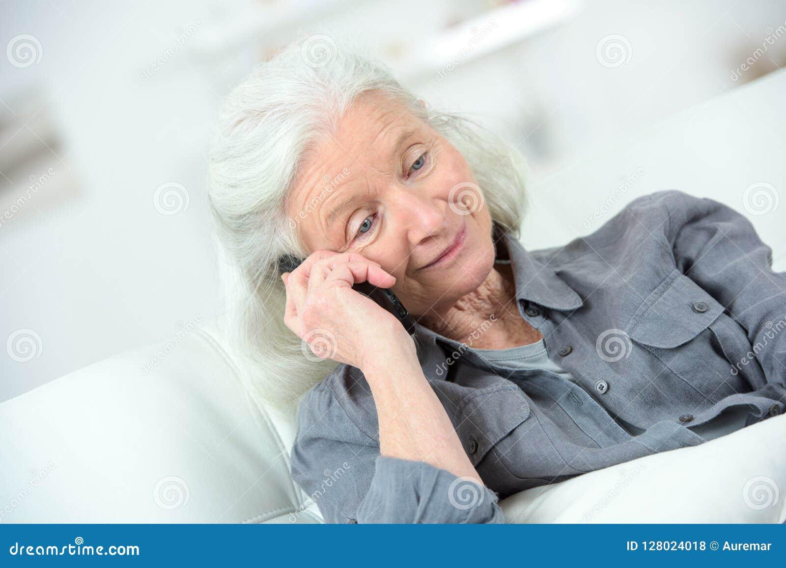 Donna anziana che per mezzo del telefono