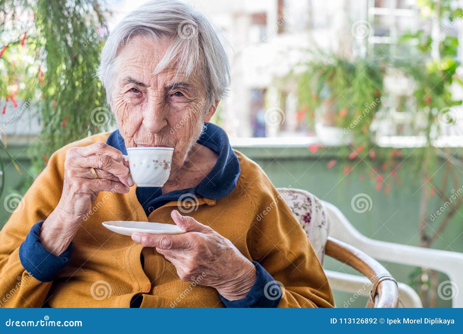 Donna anziana che si siede e che beve caffè turco nel balcone un giorno soleggiato