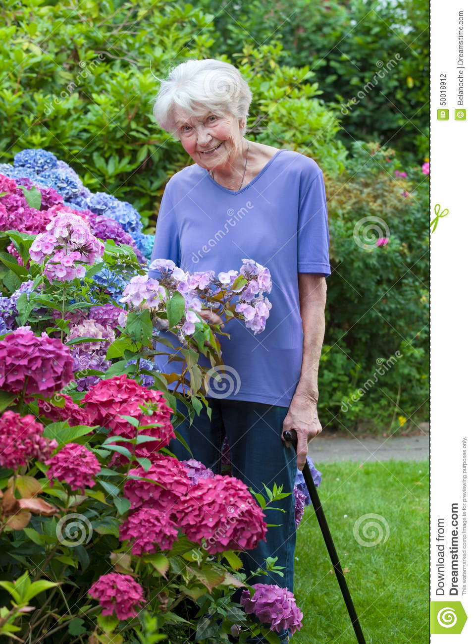 Donna anziana con Cane Posing Beside Pretty Flowers