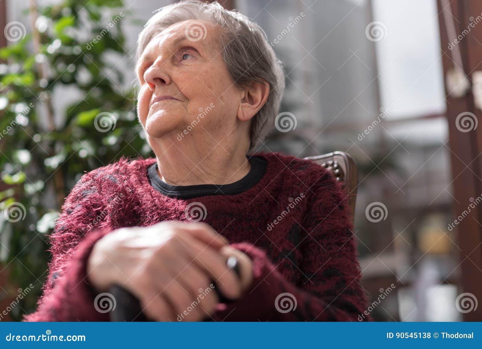 Donna anziana con le sue mani su una canna
