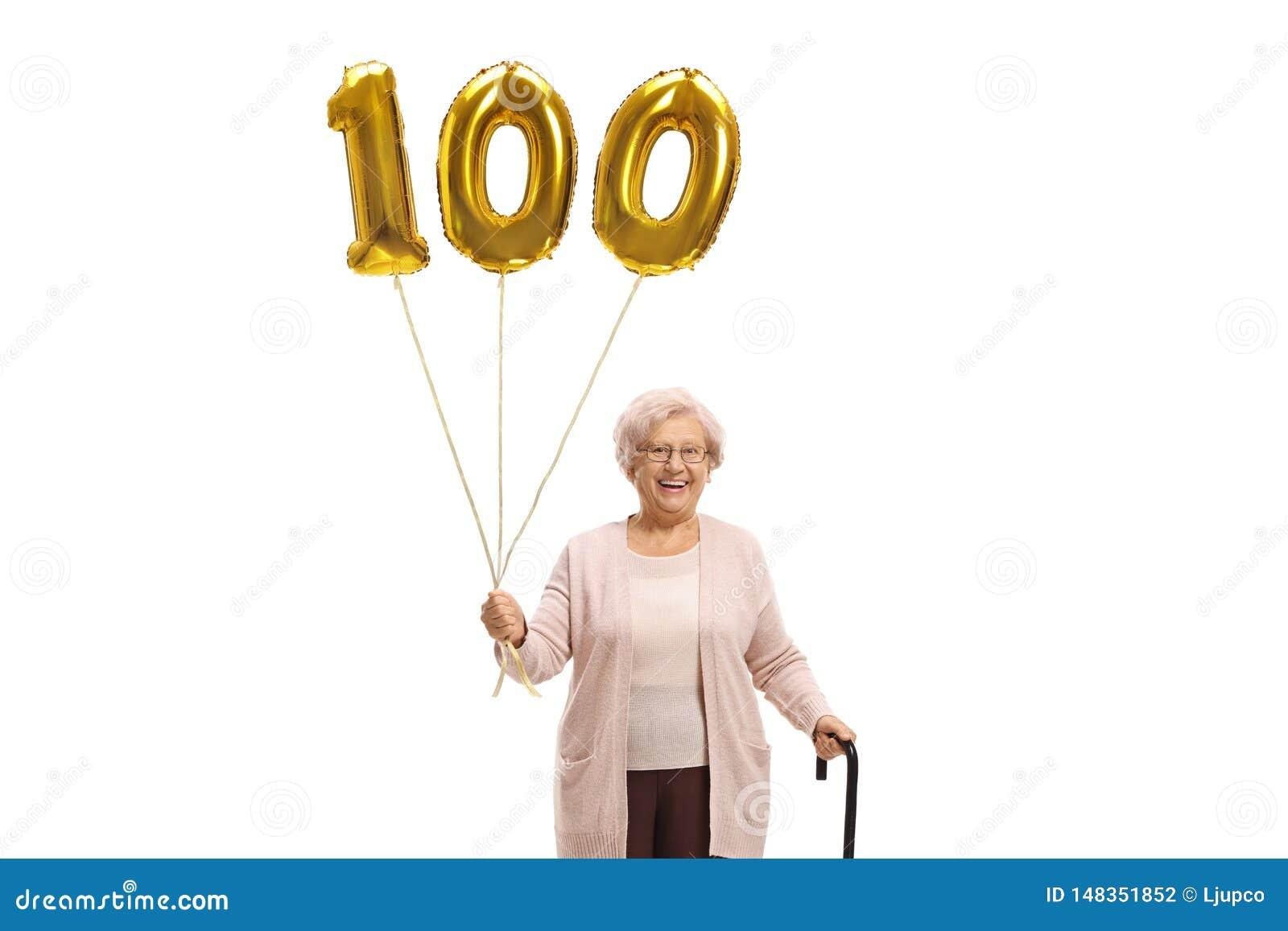 Donna anziana con un pallone dorato di numero cento e una canna di camminata